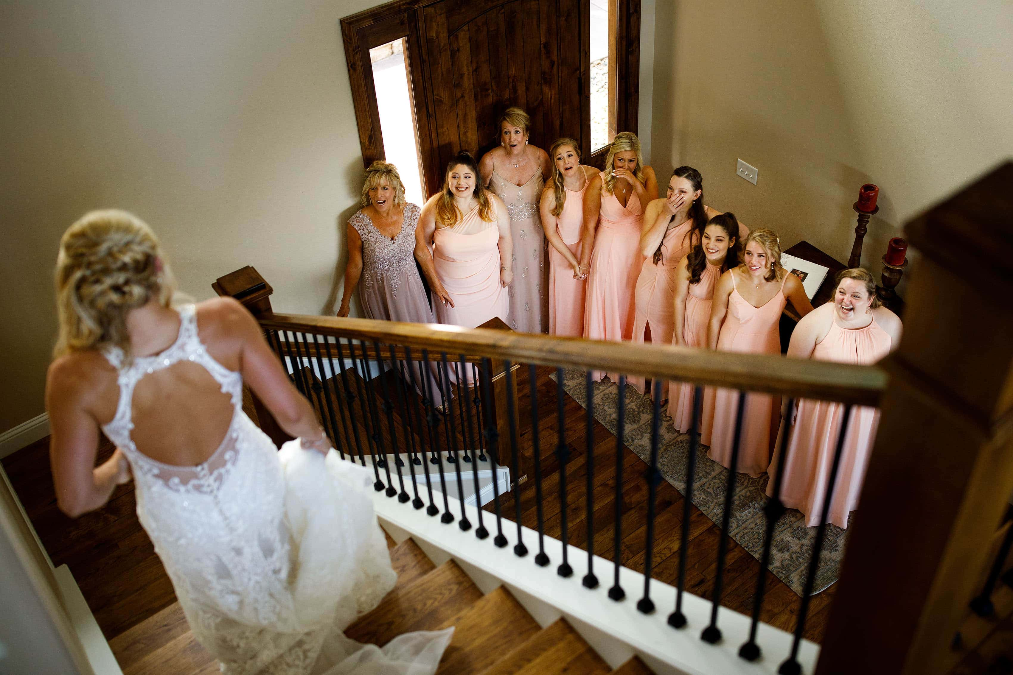 The bride descends a staircase as bridesmaids look on