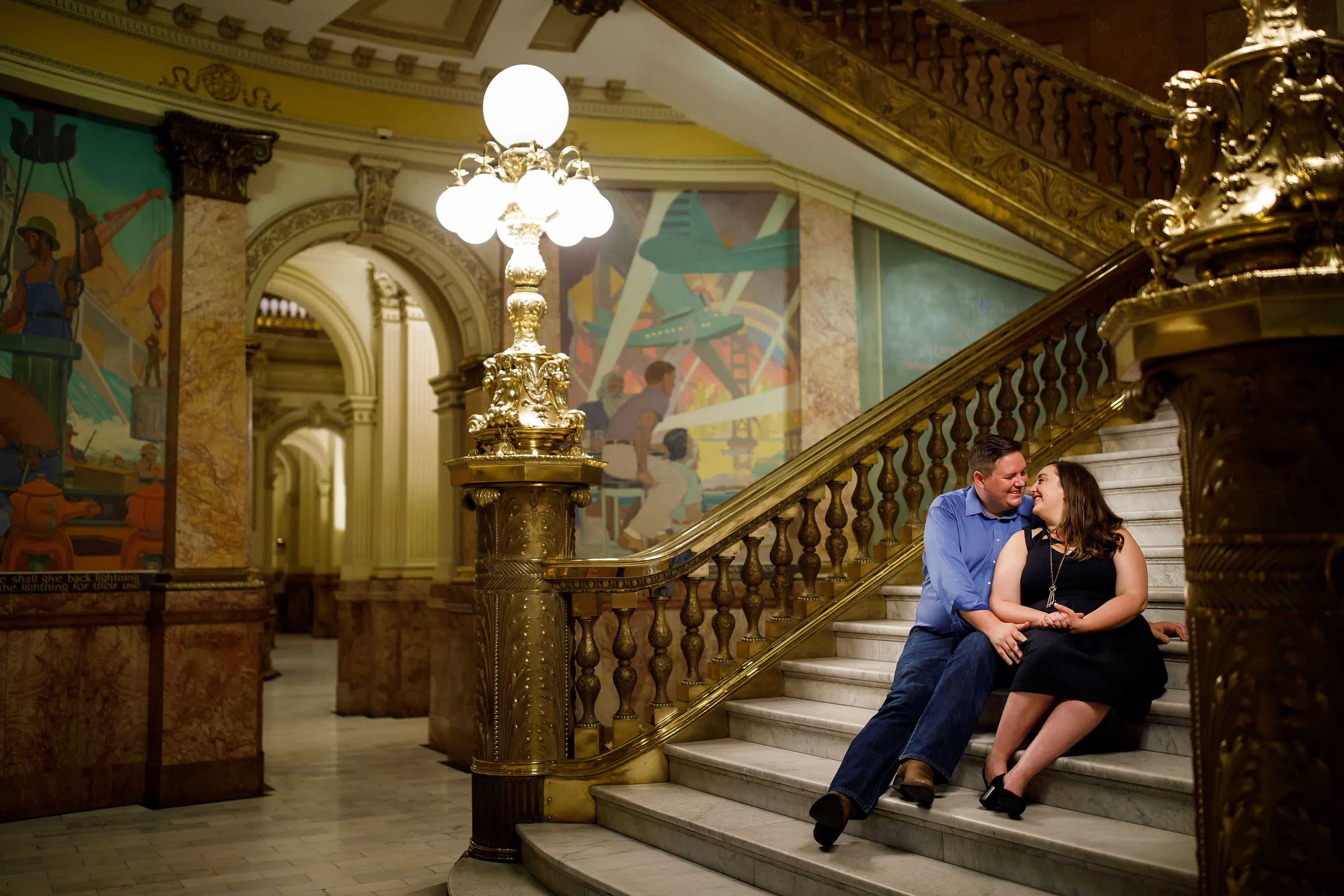 A couple sitting on the steps inside the Colorado State capitol during their engagement session in Denver