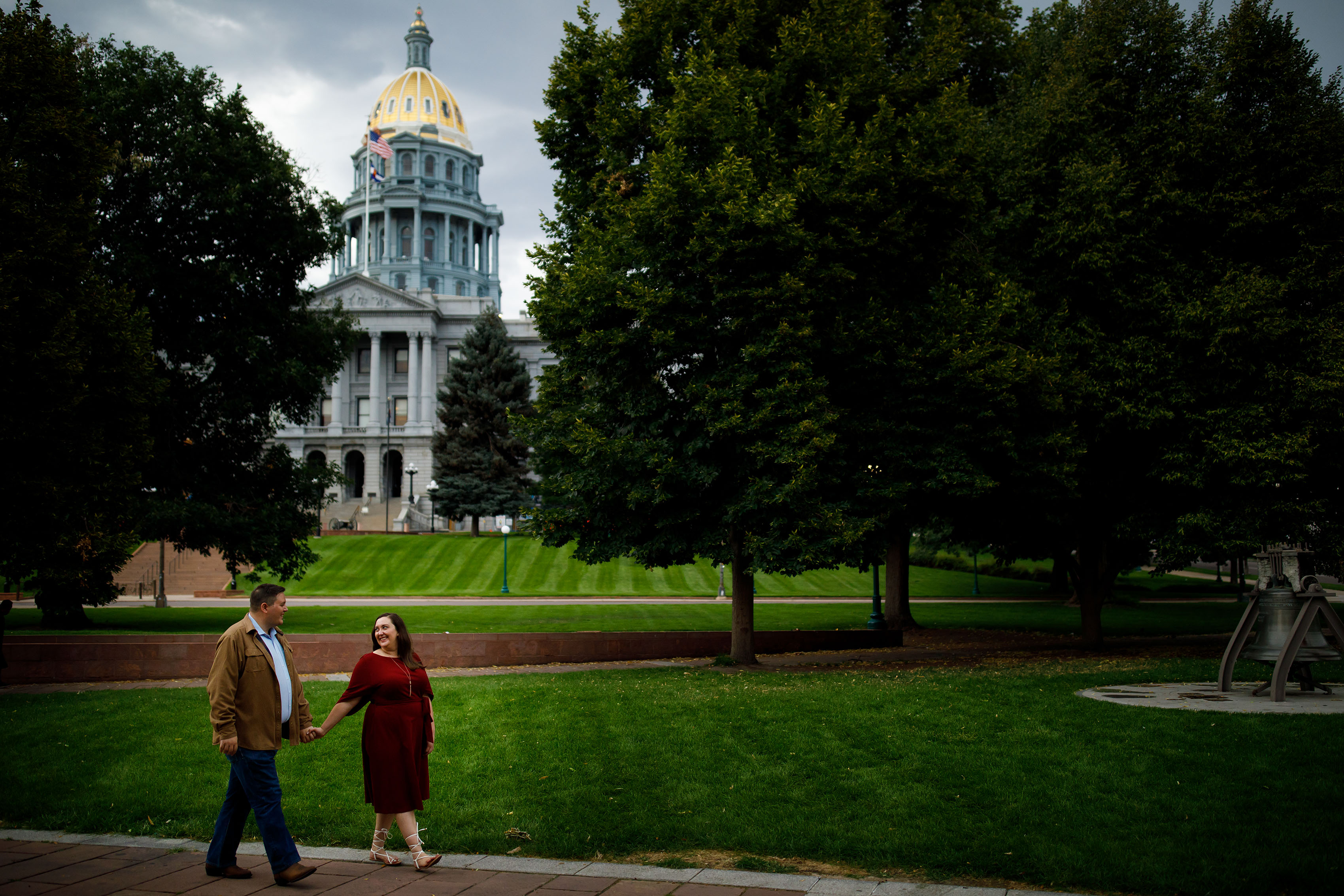 A couple walks past the Colorado State Capitol during their engagement