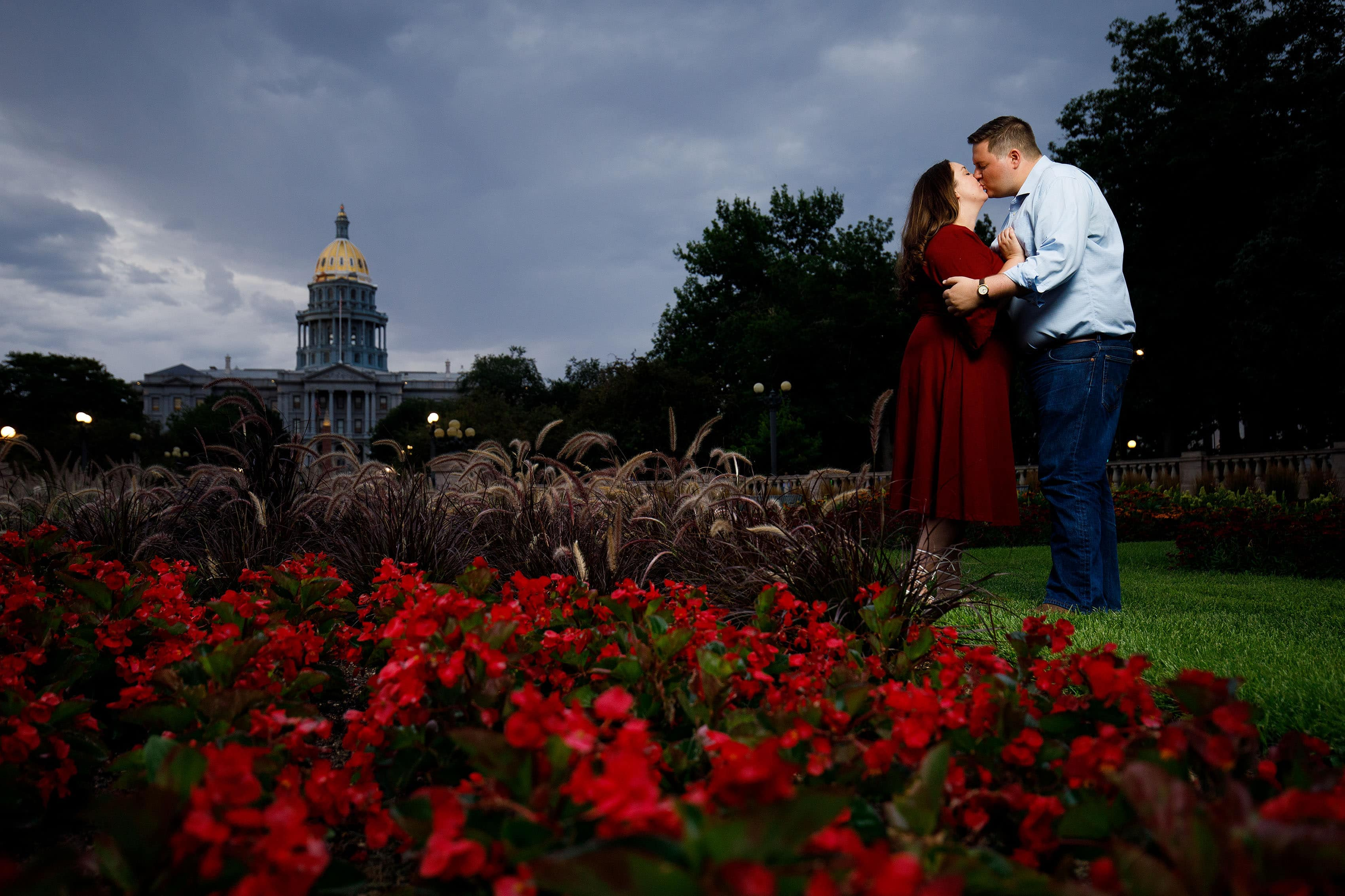 Matt and Katie kiss in Civic Center Park with the Colorado State Capitol in the background