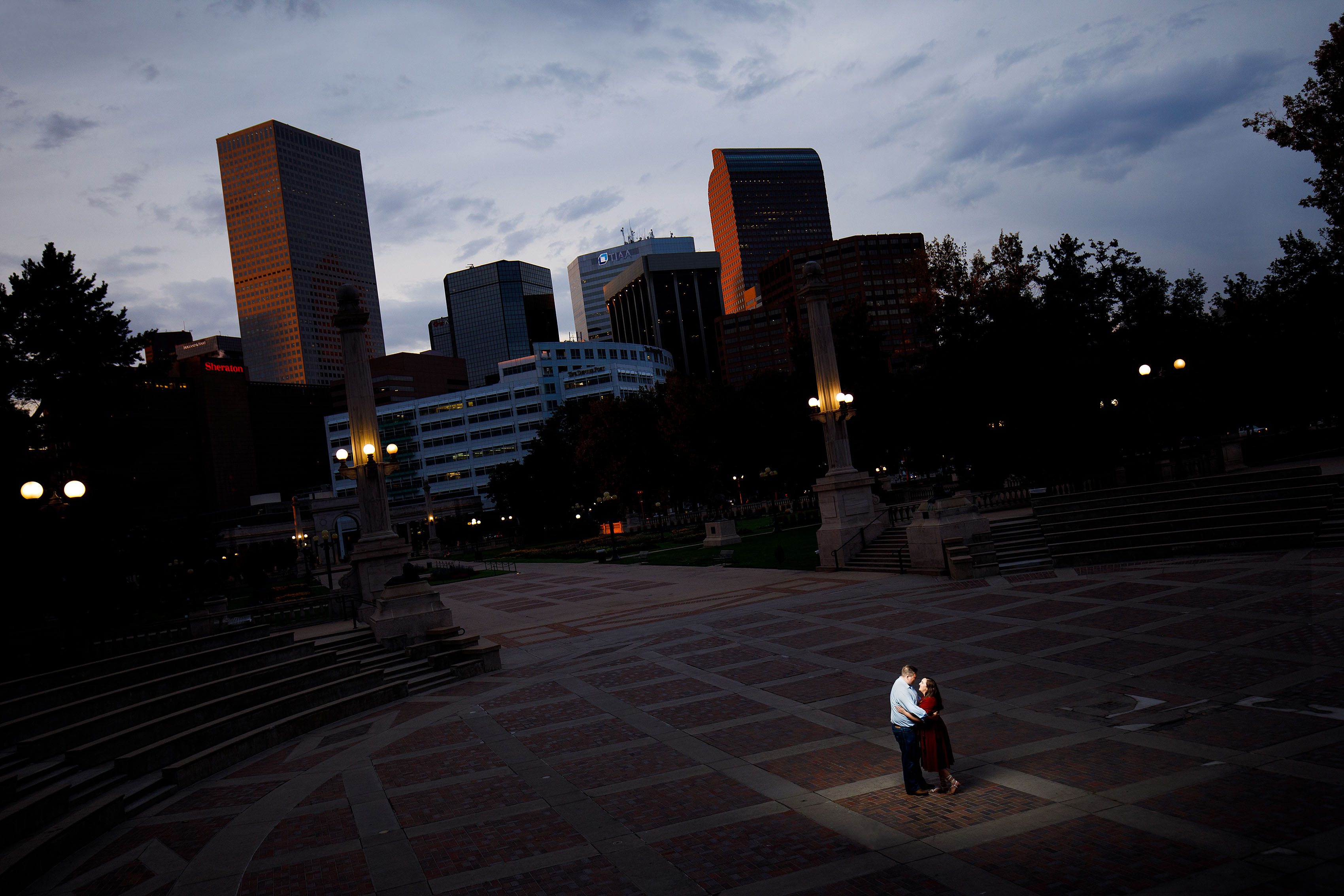 Matt and Katie share a moment in the Civic Center Park ampatheatre as the sun illuminates the Denver skyline and cash register building