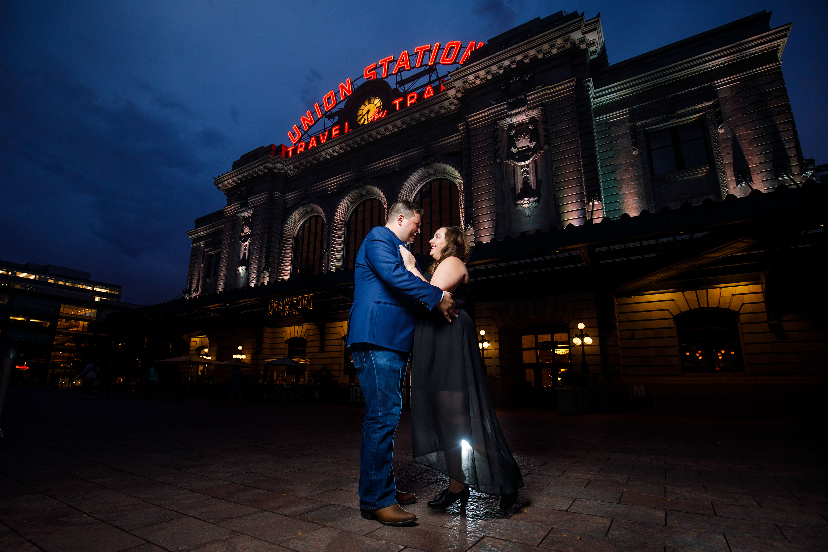 A couple pose in front of Denver Union Station at twilight