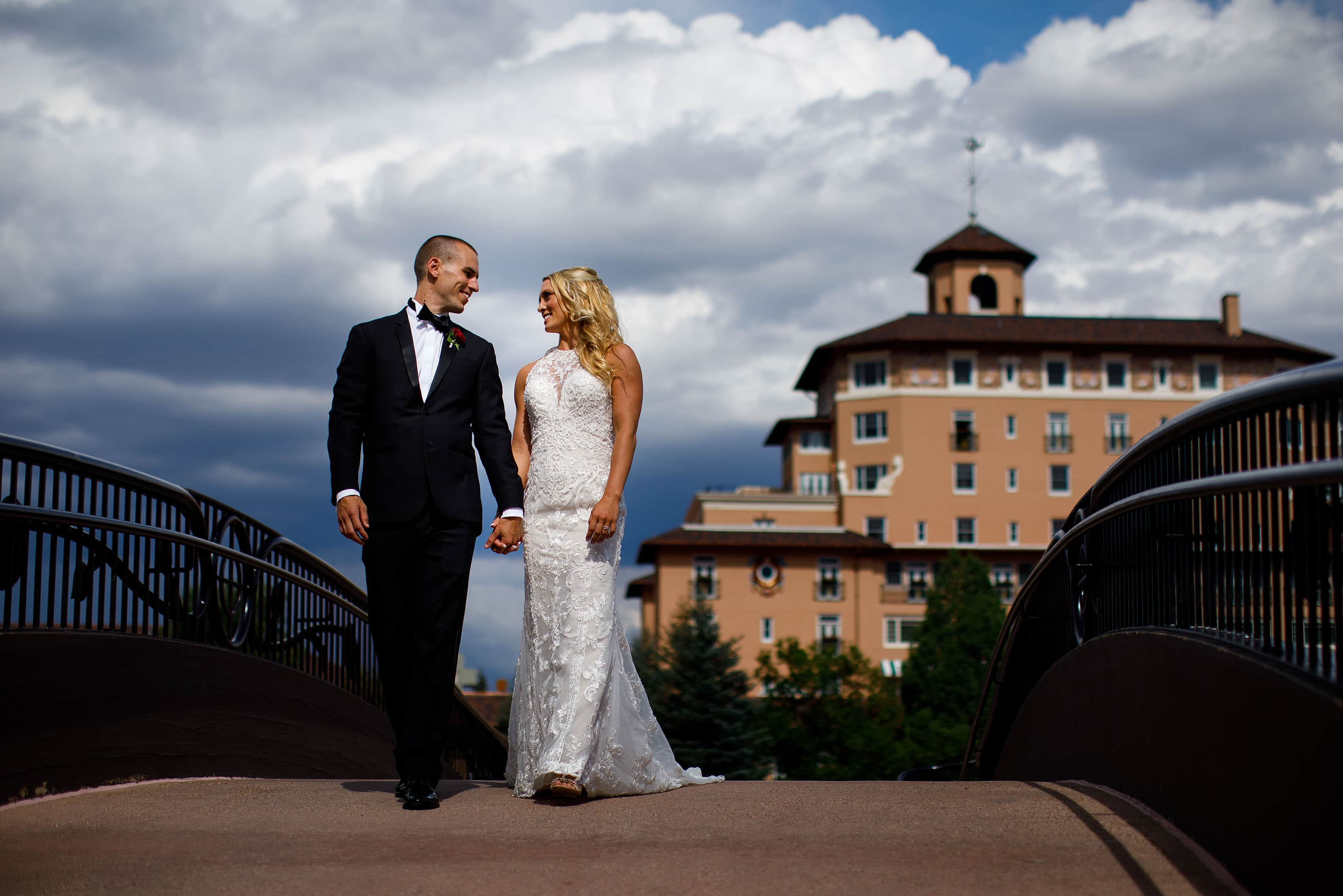 Bride and groom walk on the bridge at The Broadmoor
