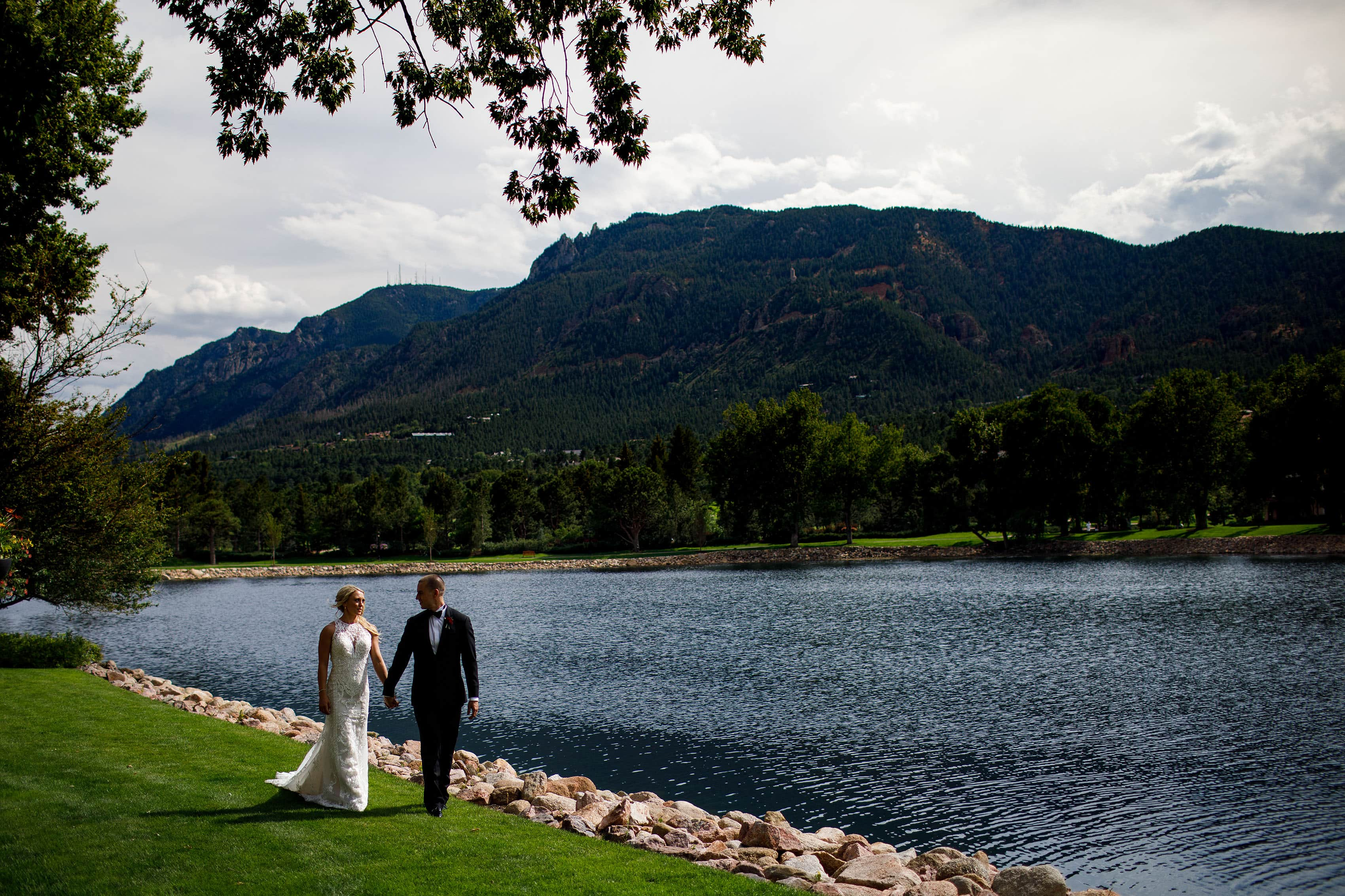 Bride and groom walk by Cheyenne Lake at The Broadmoor