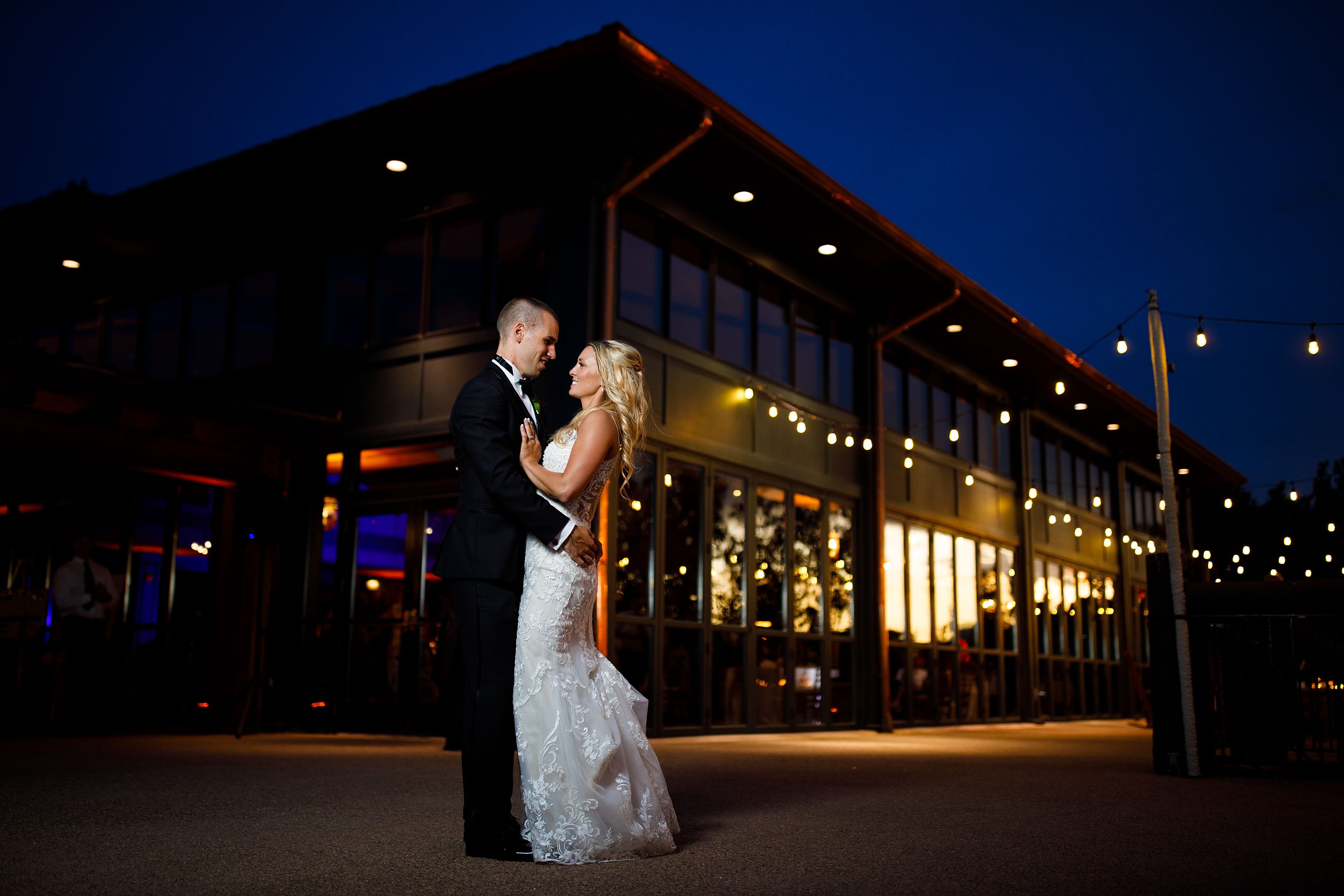 Bride and groom pose on the patio at Cheyenne Lodge at twilight