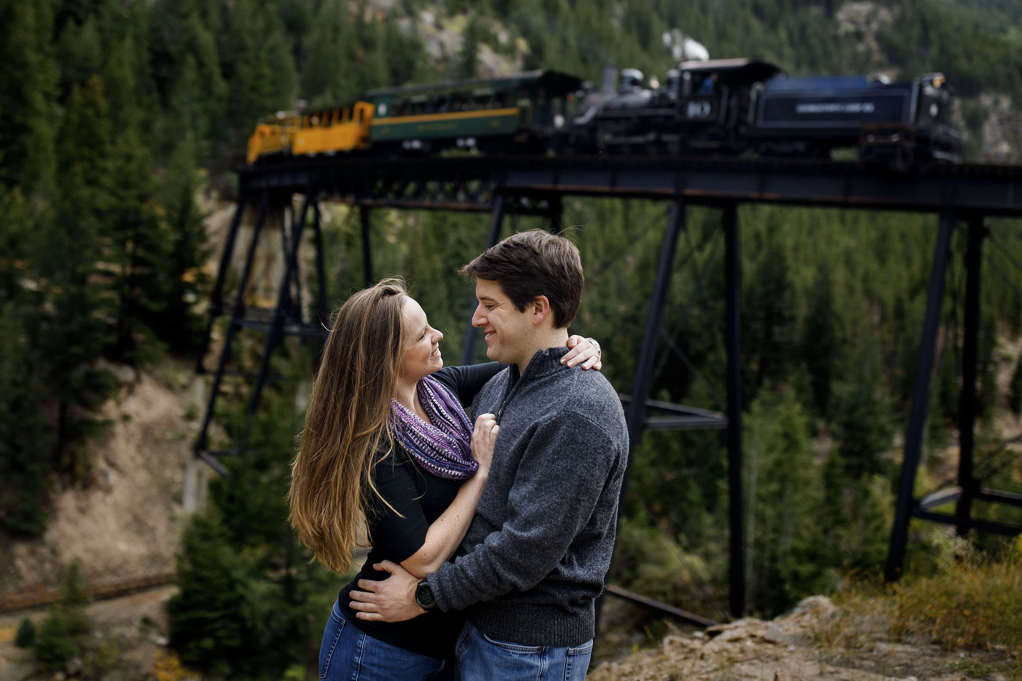 Chris and Madeline embrace as the Georgetown Loop Railroad passes by during their engagement session