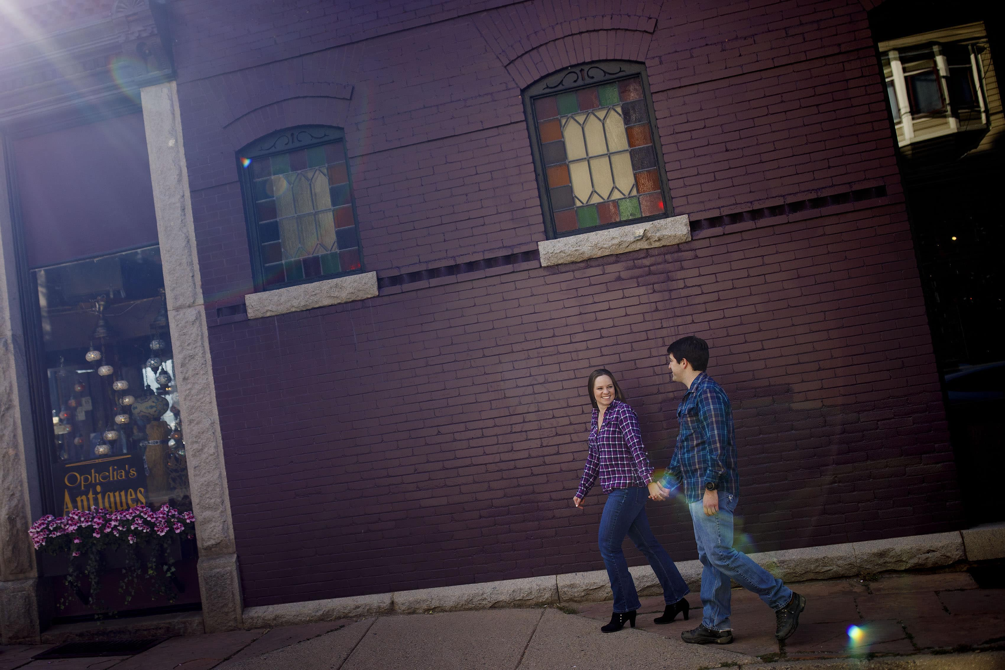 A couple walks by Ophelia's Antiques in Georgetown, Colorado during their engagement photos