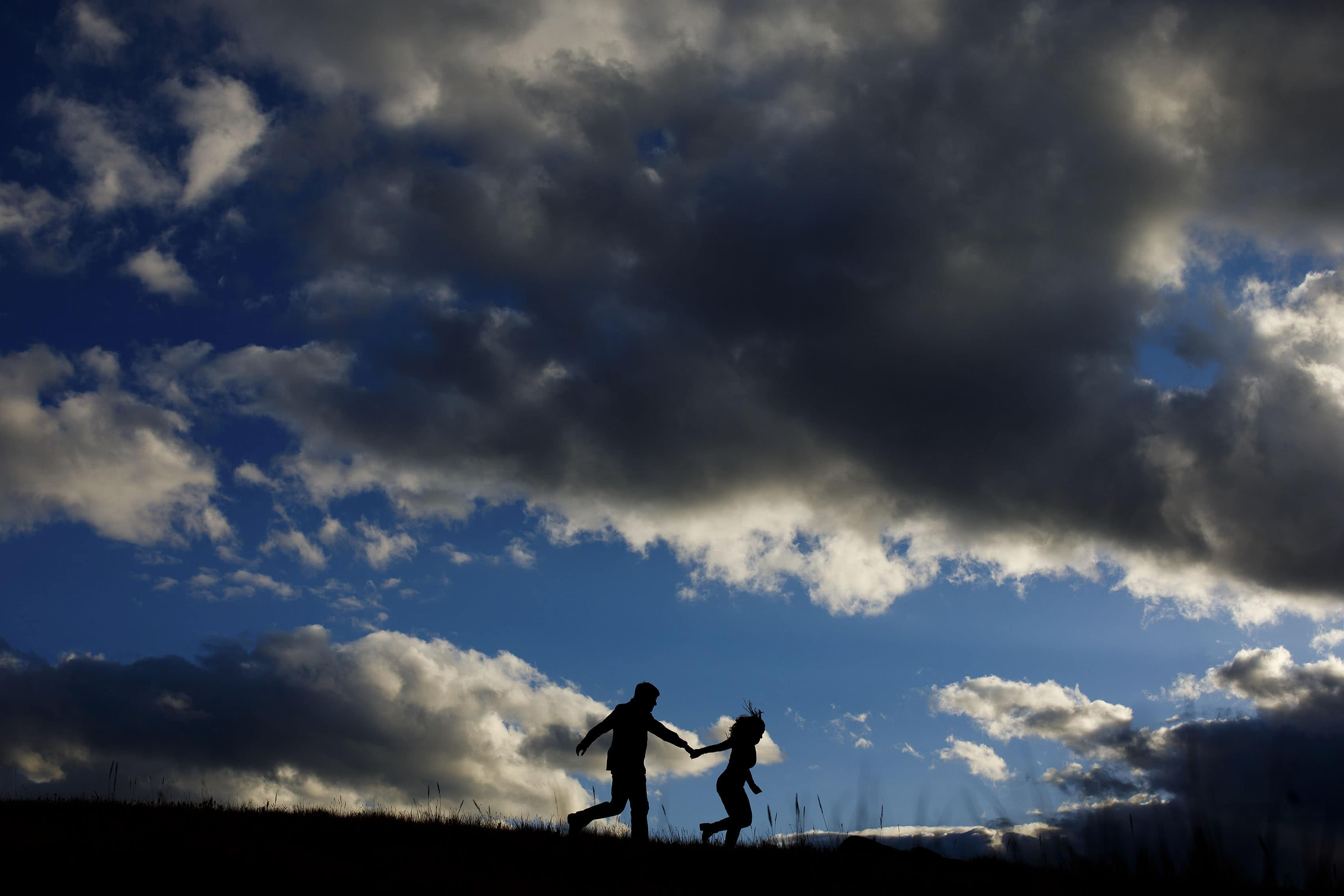 Silhouette of a couple running together during engagement photos
