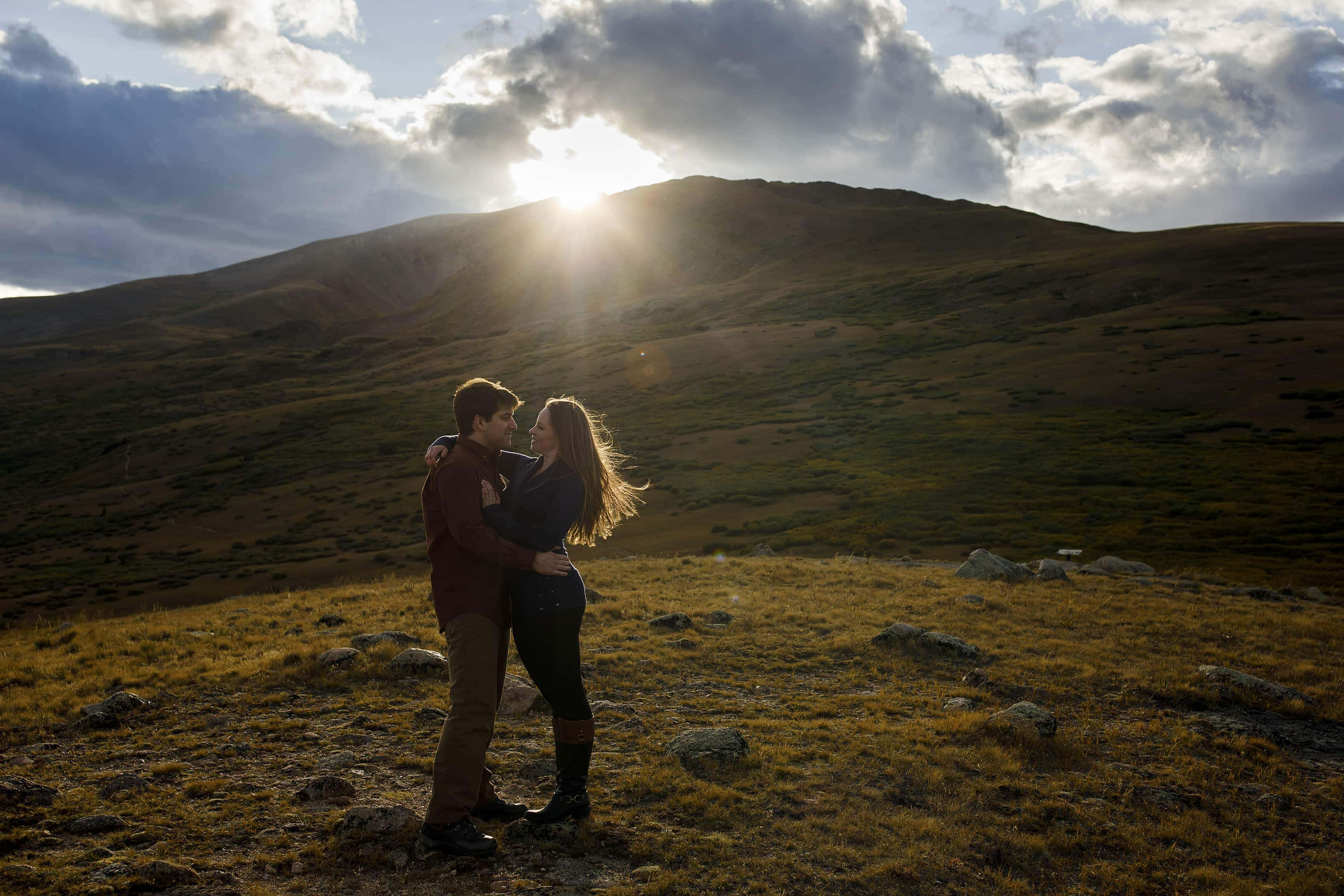 The sun sets over Square Top Mountain as a couple poses during their engagement photos at Guanella Pass