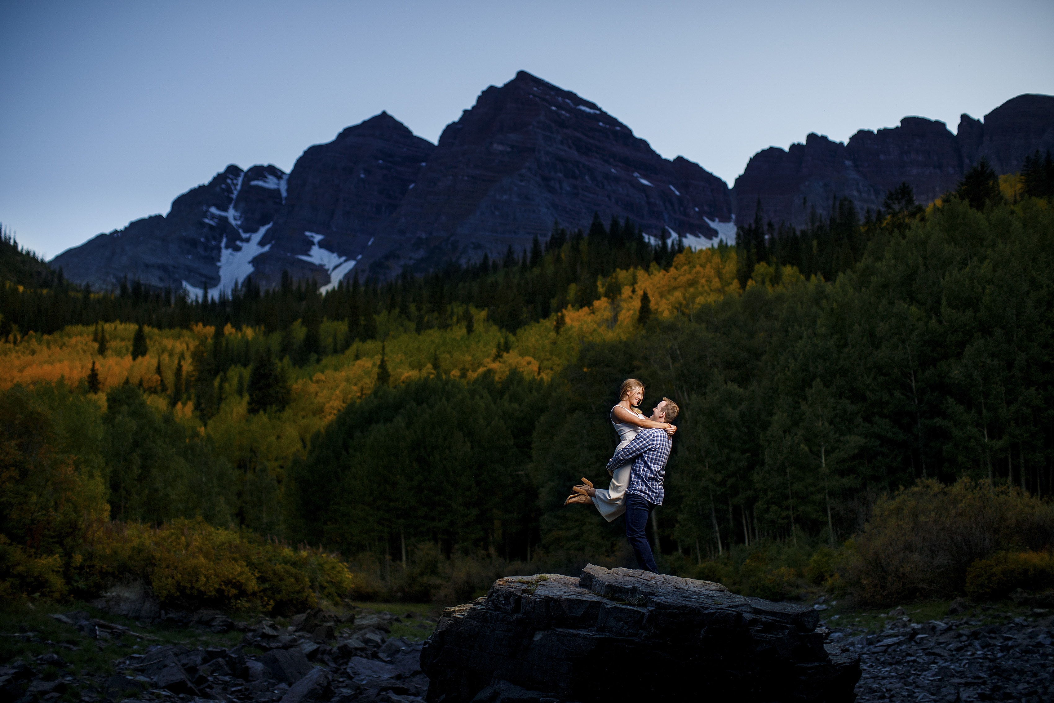 Mel and Drew share a moment during their Maroon Bells engagement session with fall colors nearby during twilight in Aspen, Colorado.