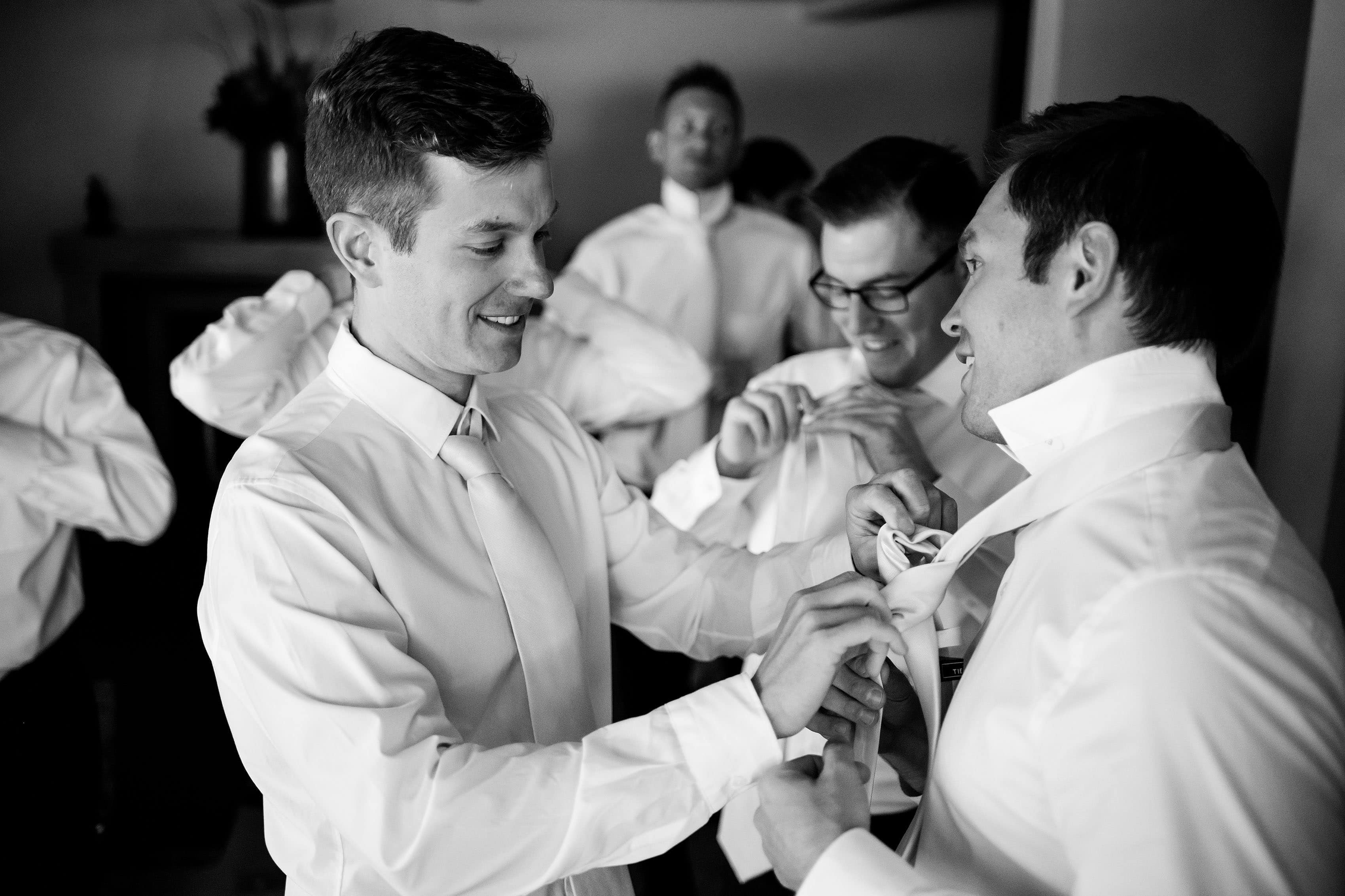 The groom helps groomsmen get ready before the wedding