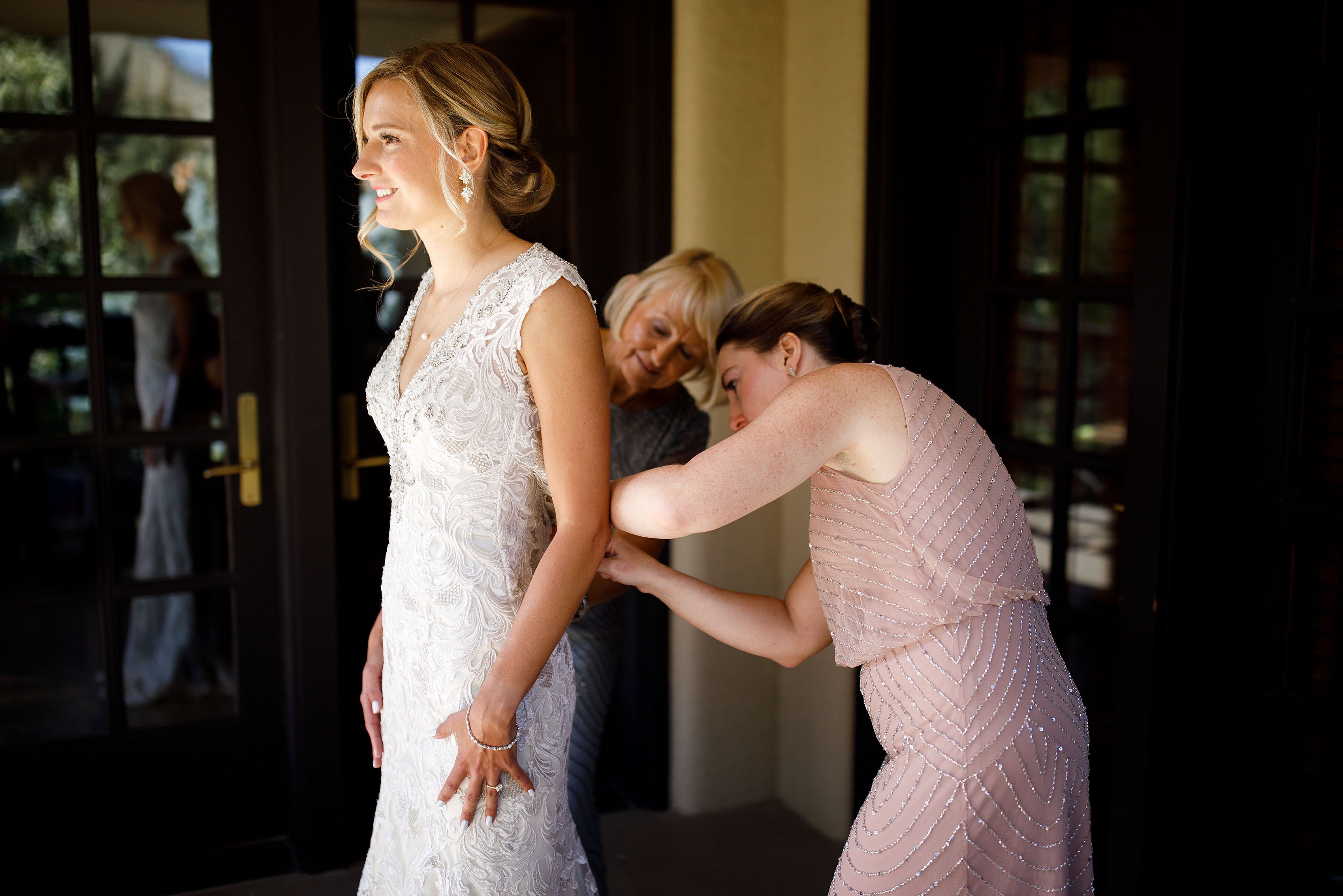 Melissa gets help buttoning her wedding dress