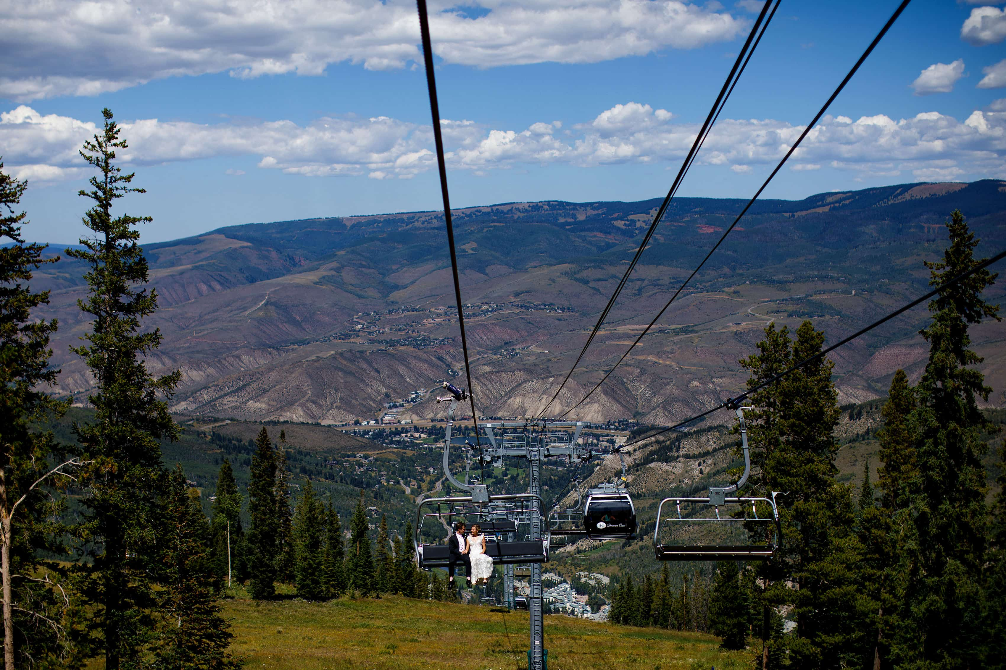 The bride and groom ride the Centennial Express chairlift on their wedding day in Beaver Creek