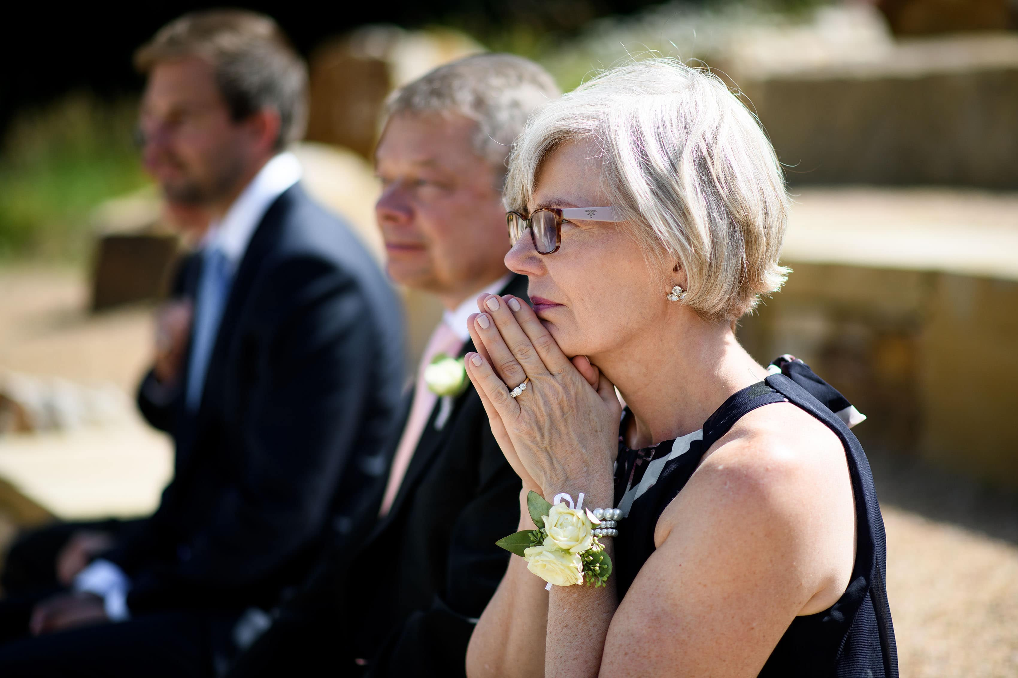 Mother of the groom reacts during the ceremony