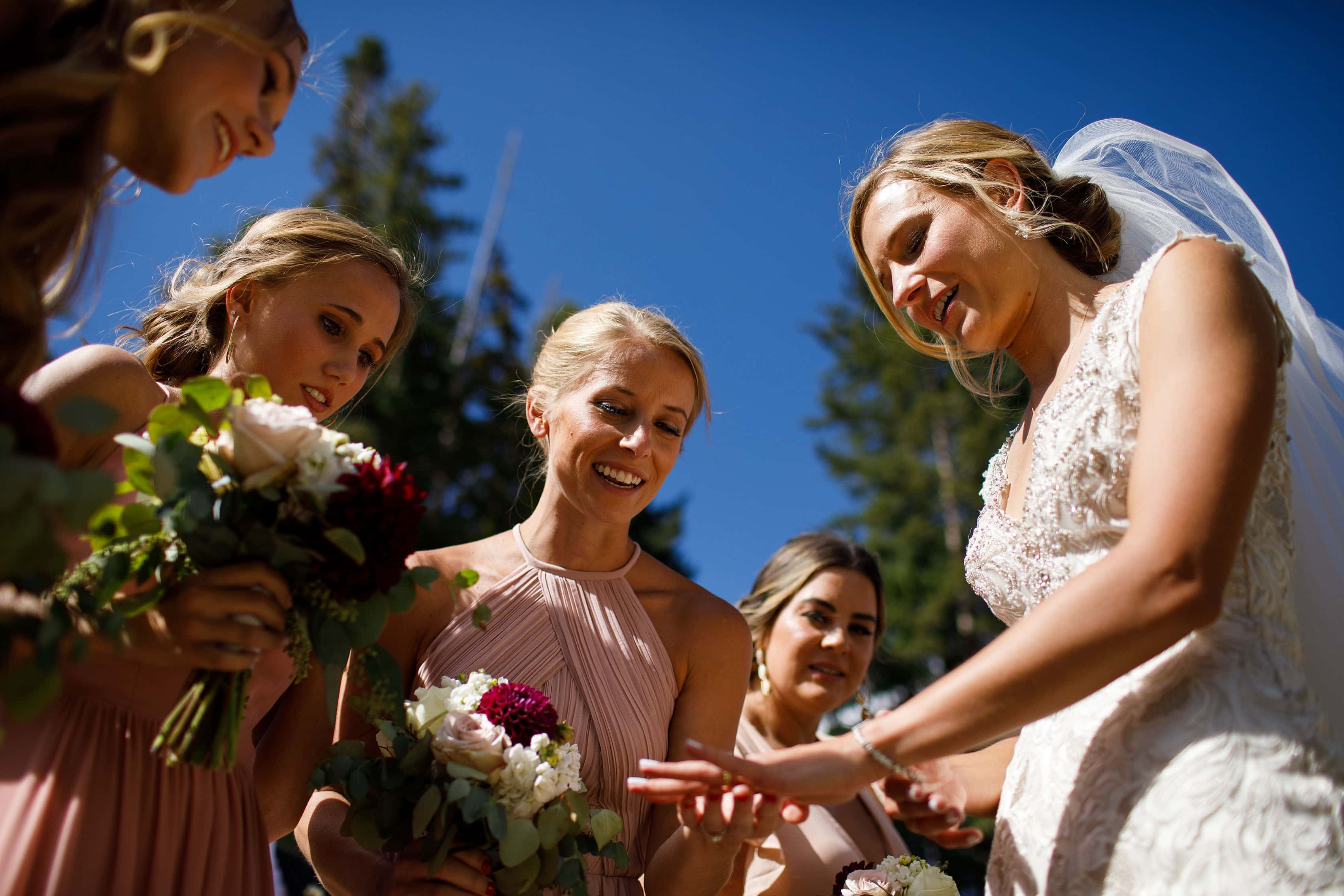 The bride shows off her new wedding ring to the bridesmaids