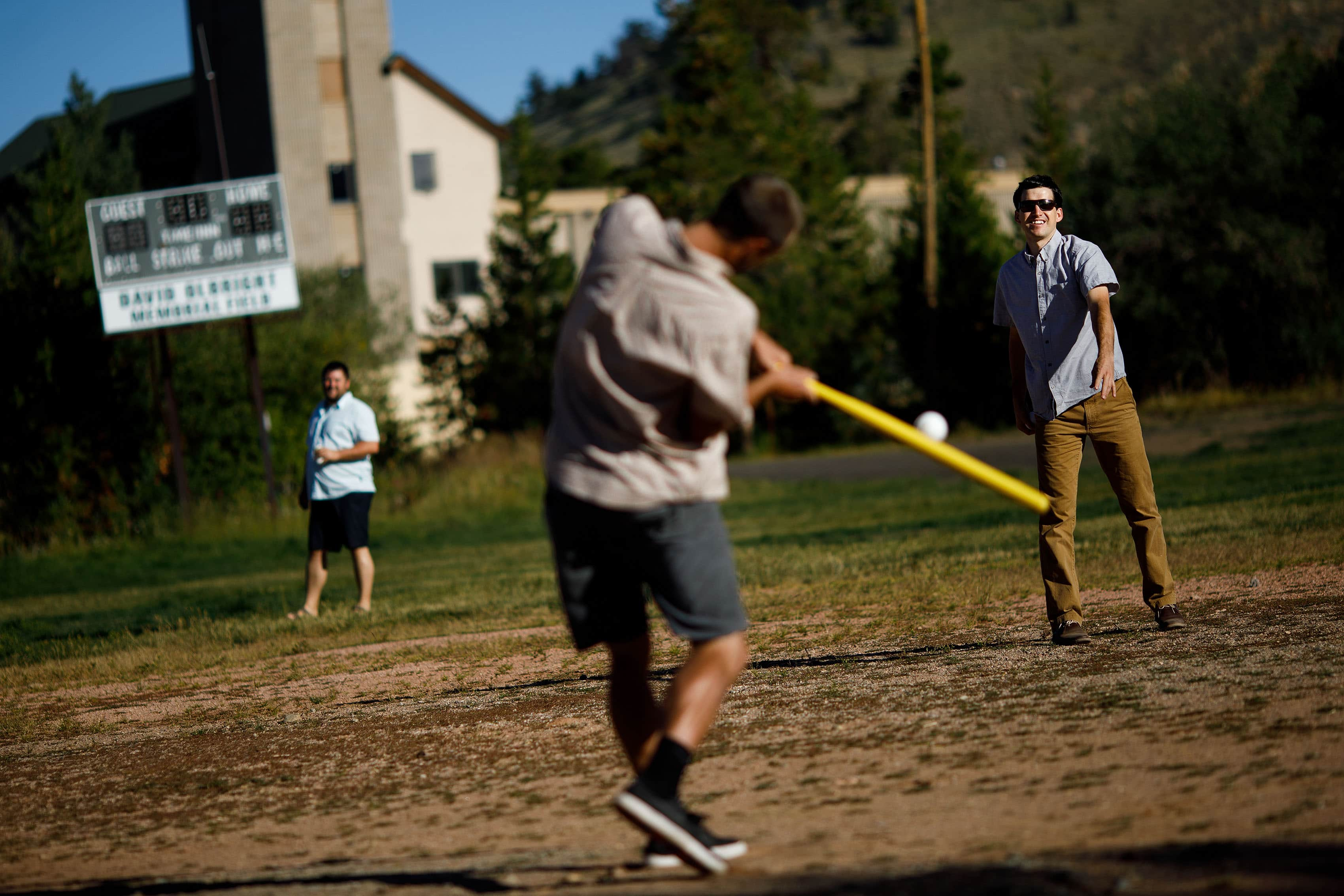 Groomsmen playing wiffle ball in Dillon, Colorado