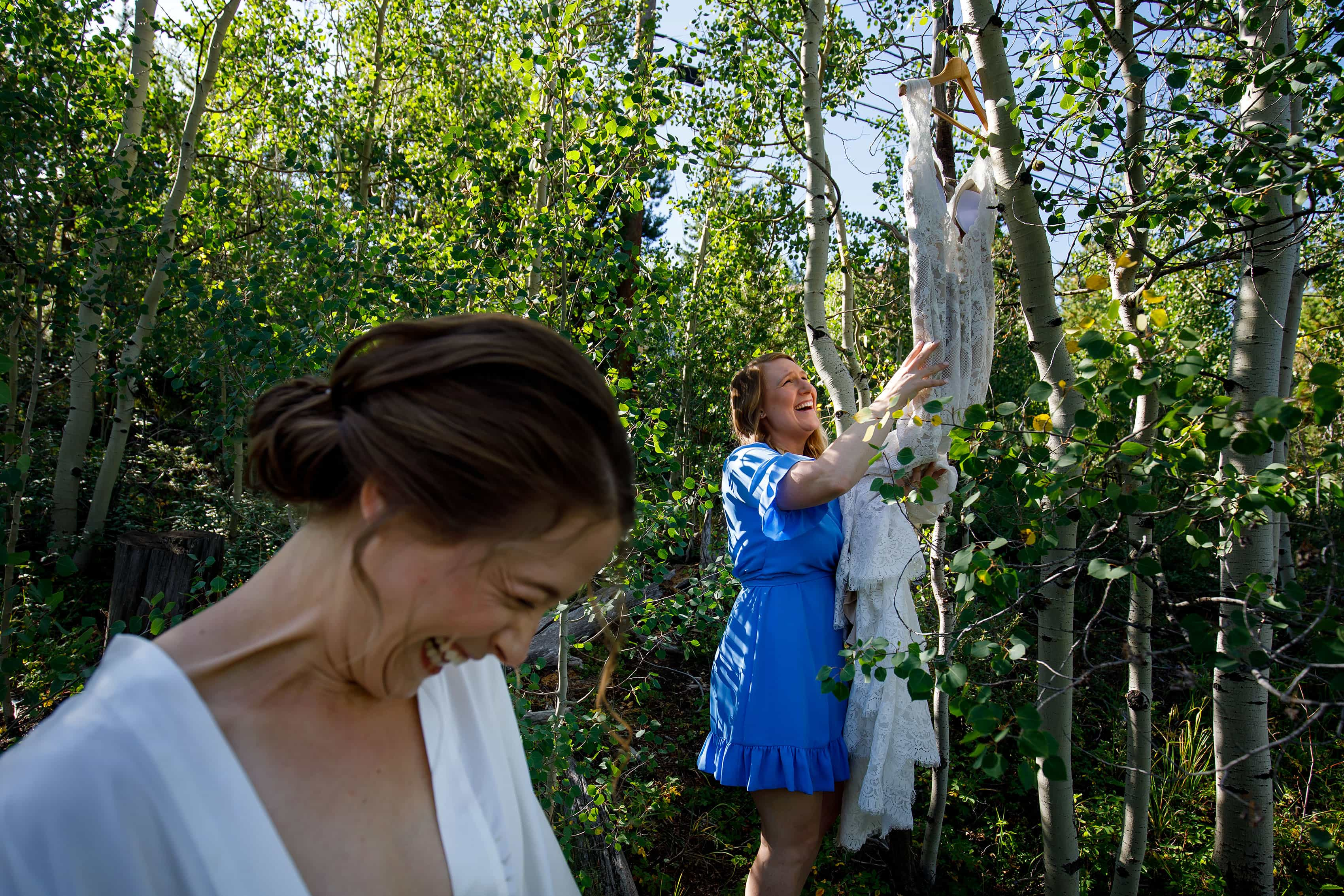 The bride and cousin laugh while trying to get the dress down from a tree