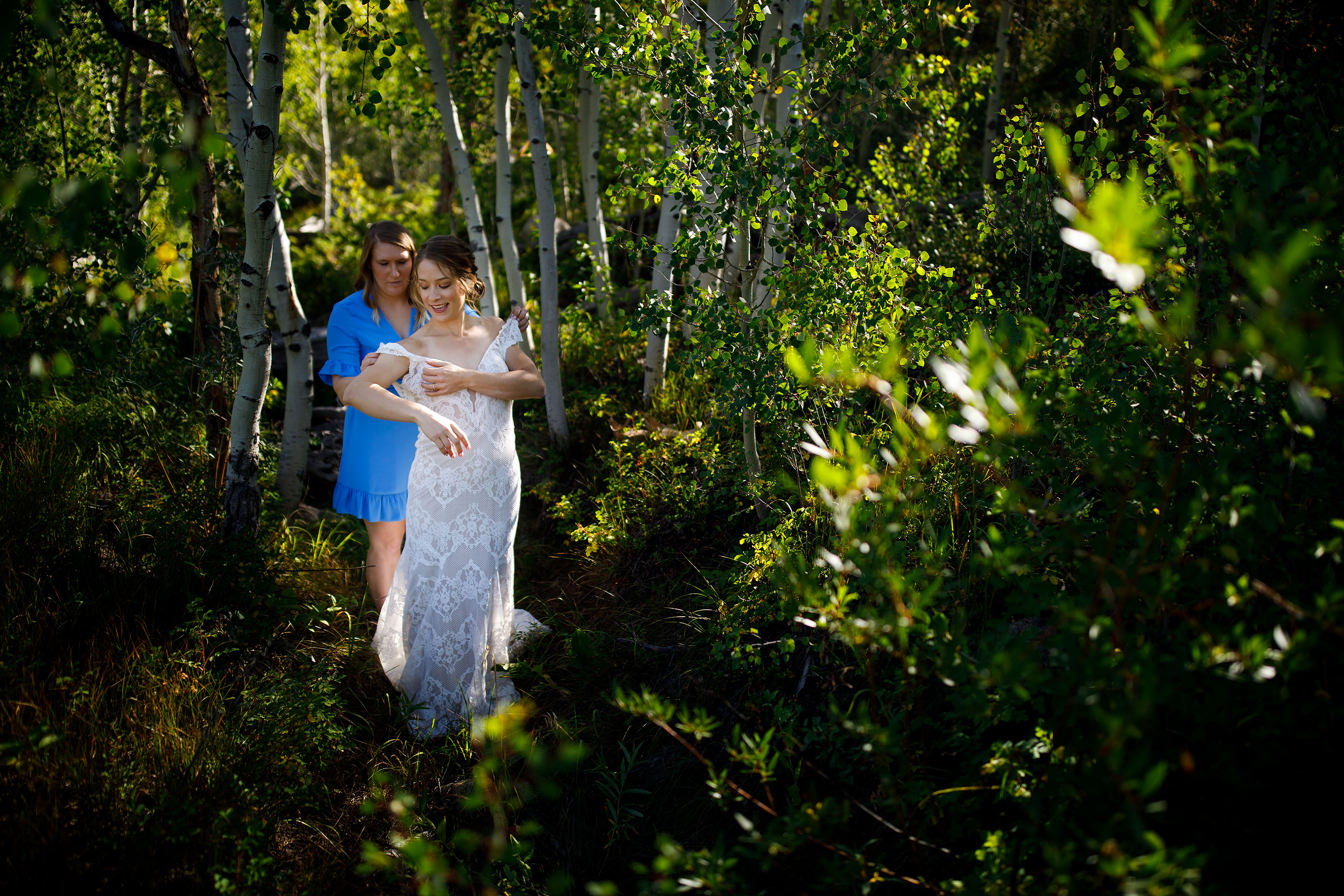 Carissa gets help putting her wedding dress on in an aspen grove