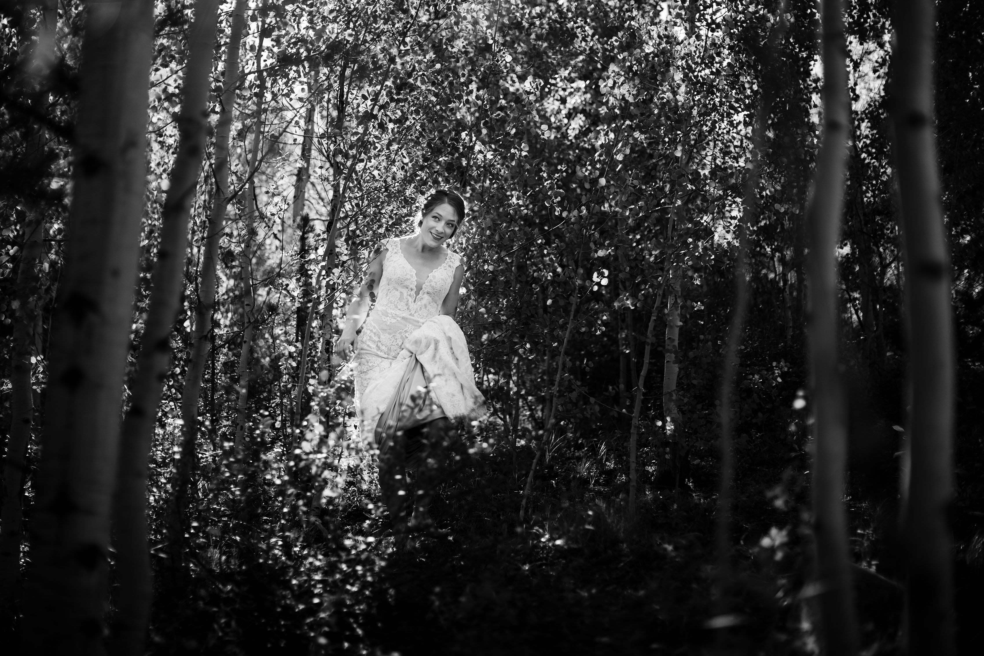 The bride walks through an aspen grove
