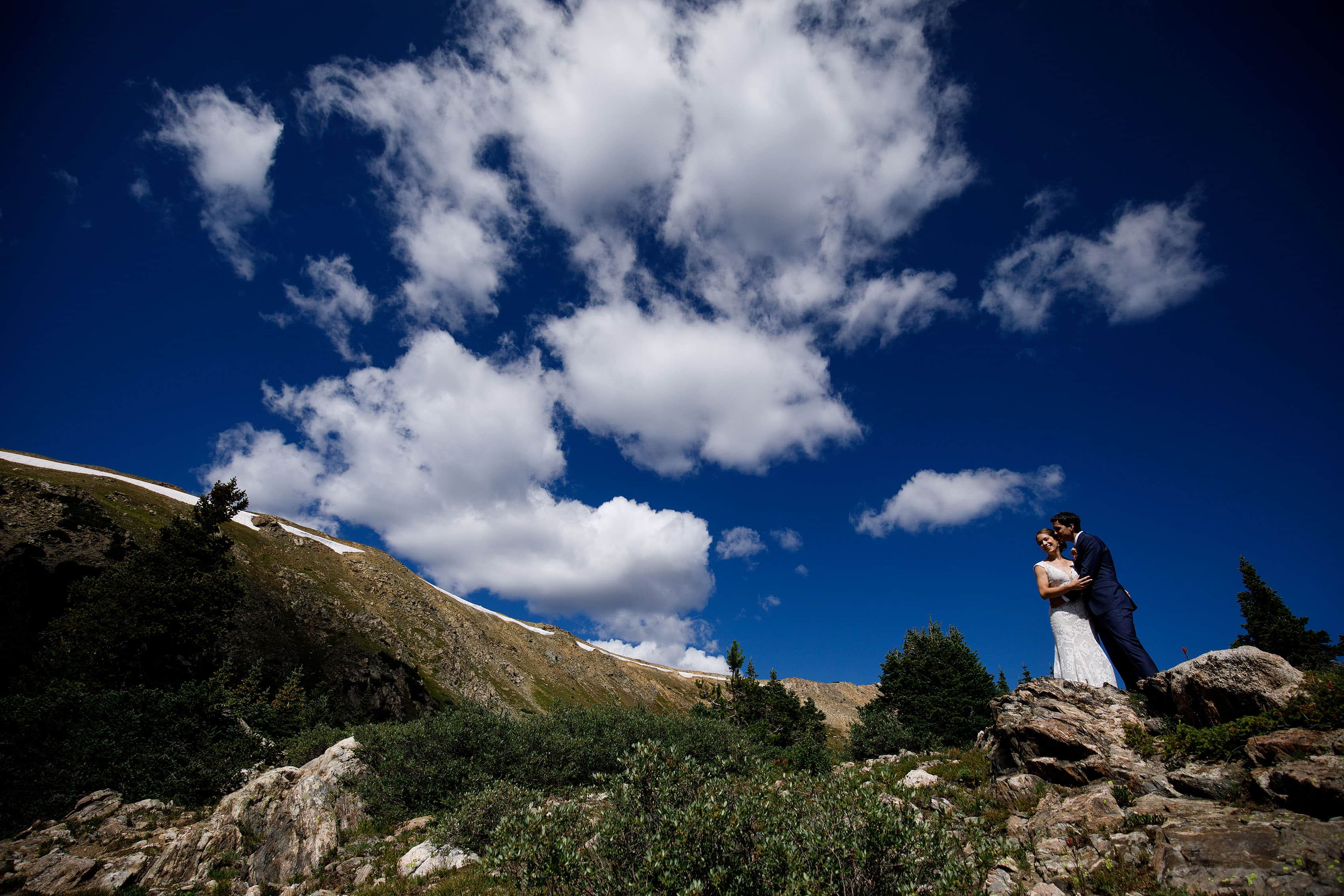 The couple embrace as clowds form above them at loveland pass