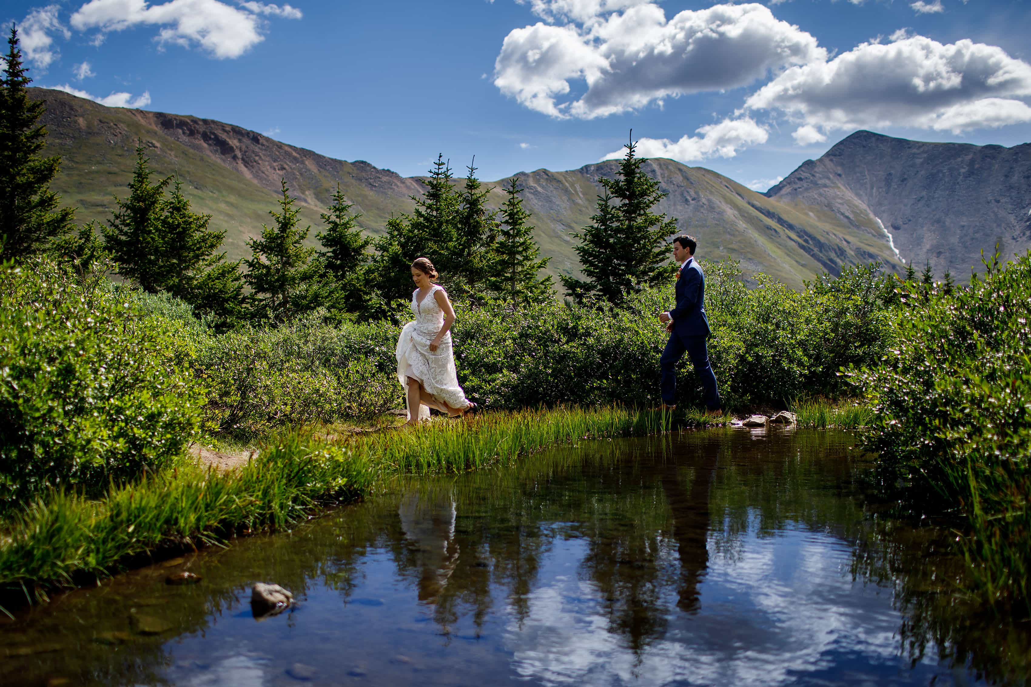 The bride and groom pass by a mountain pond on Loveland Pass during their wedding day
