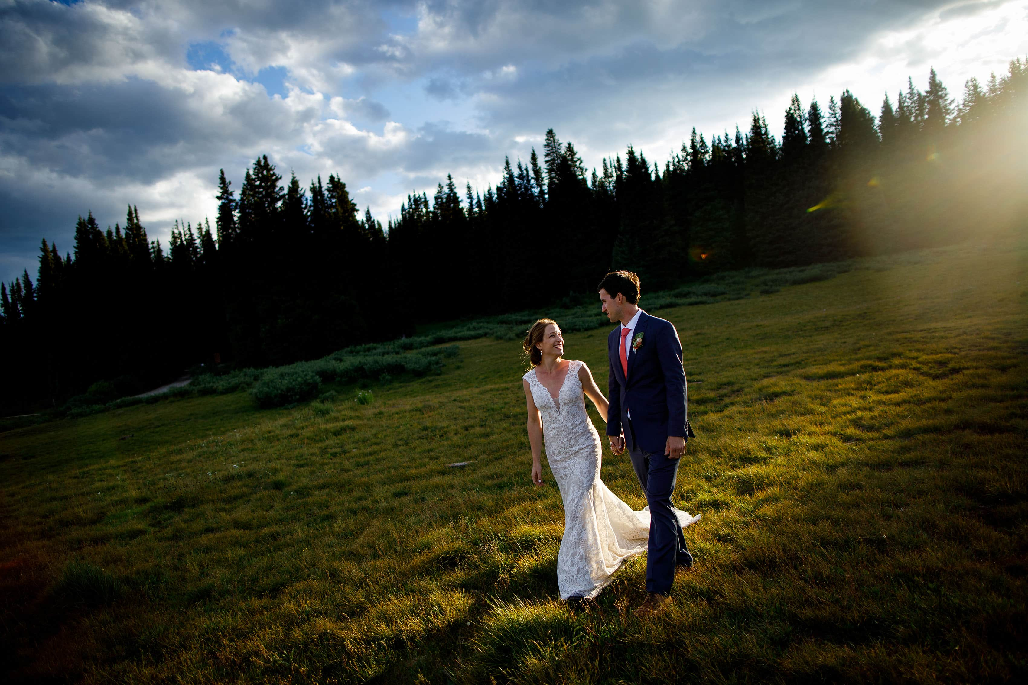 The sun flares over the ridge as Carissa and Kyle walk together at Shrine Pass
