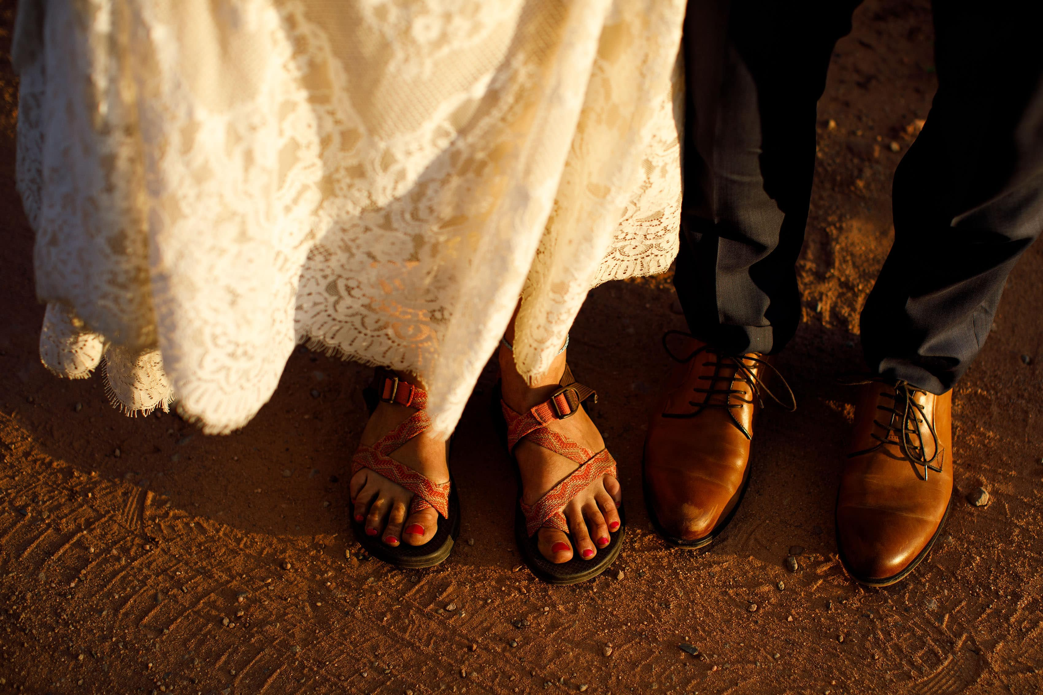 A bride and groom's footwear on the red dirt road on Shrine Pass