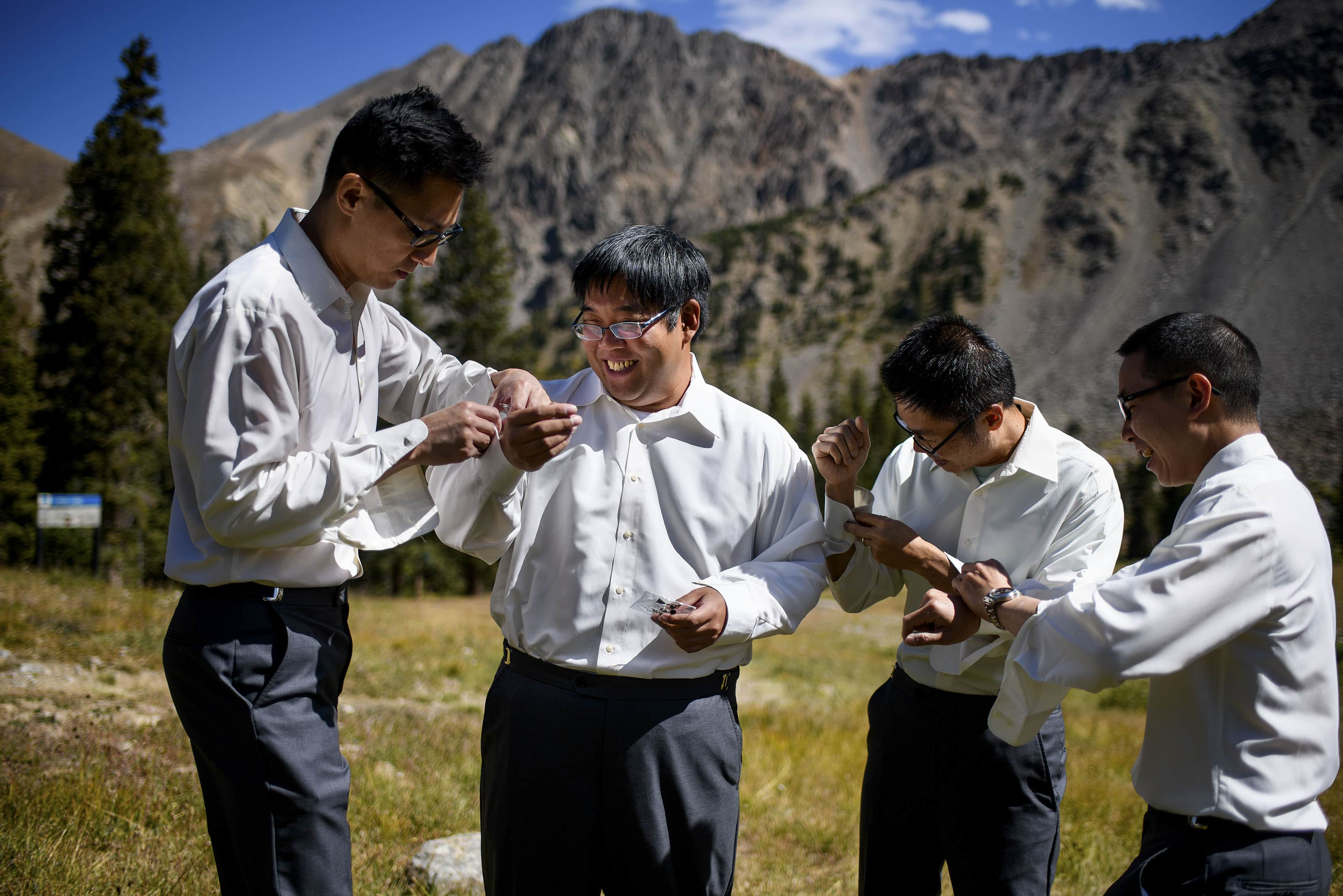 David gets dressed with his groomsmen outside at Black Mountain Lodge at Arapahoe Basin on his wedding day