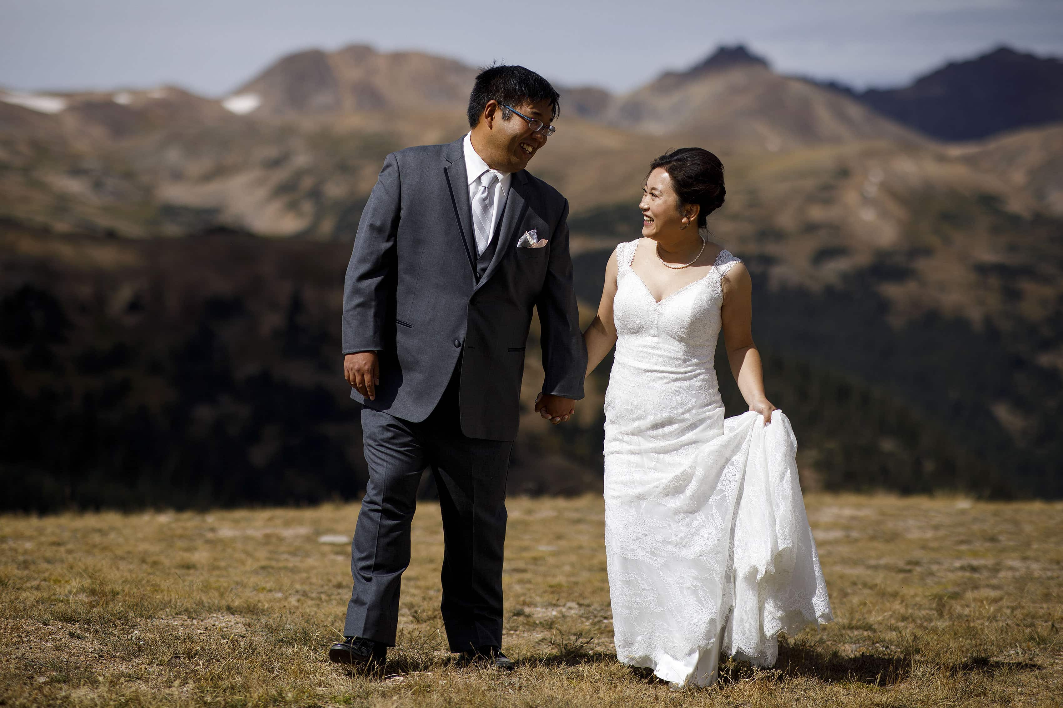David and Xinya walk together on Loveland Pass during their wedding day