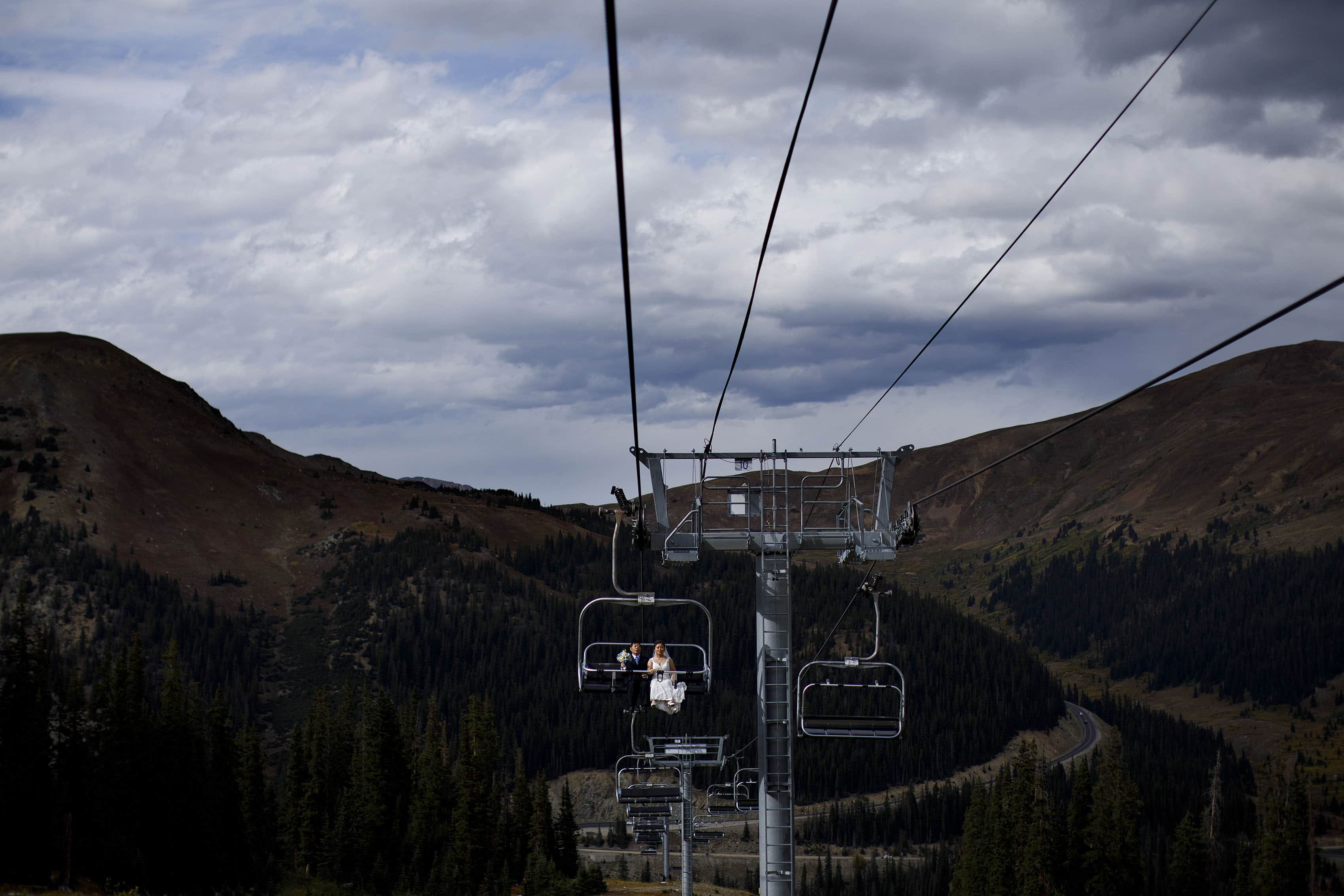 Xinya rides the Black Mountain Express chair lift with her father to the ceremony at Arapahoe Basin