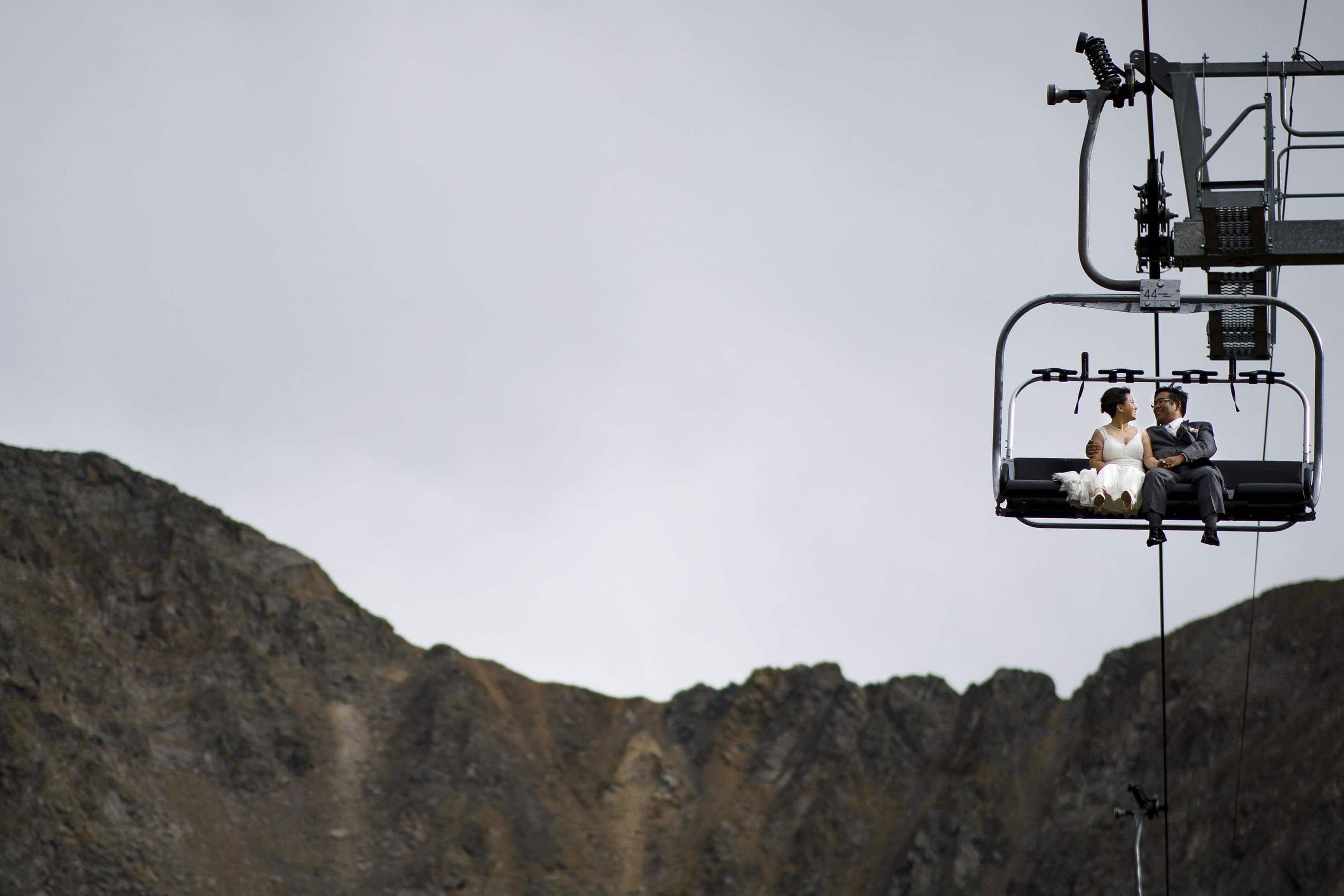A couple ride the Black Mountain Express chairlift at A Basin on their wedding day