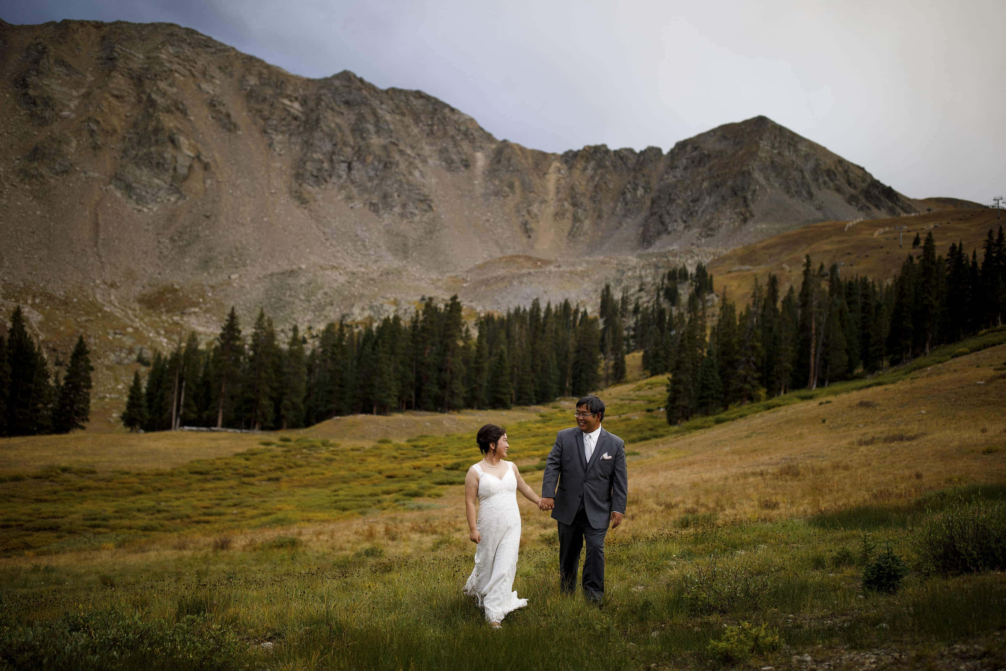 David and Xinya walks together in the field near the East Wall at A Basin during their wedding