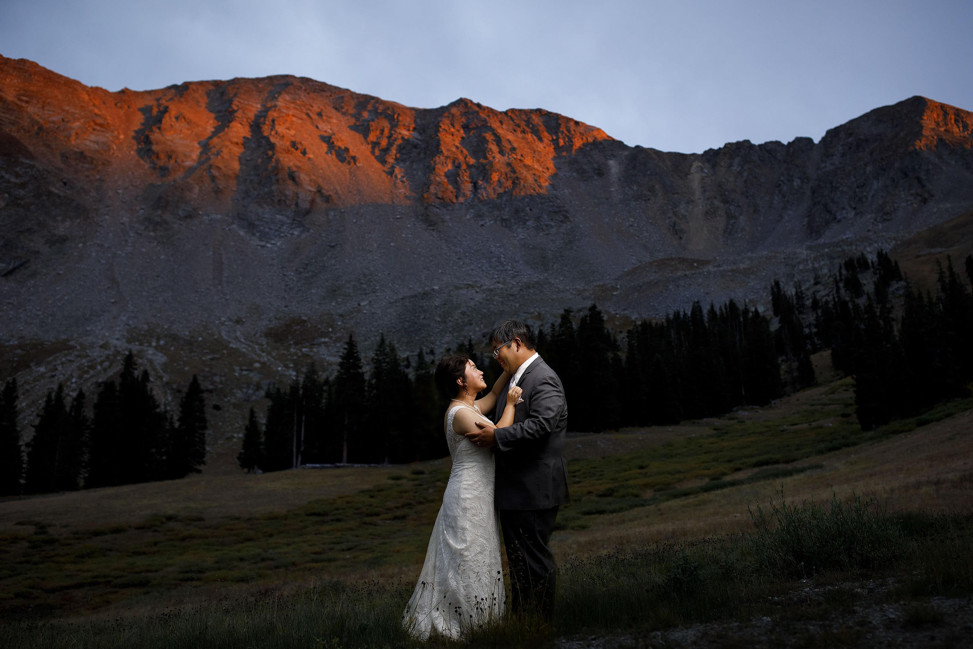A couple share a moment together as alpenglow hits the East Wall at Arapahoe Basin on their wedding day
