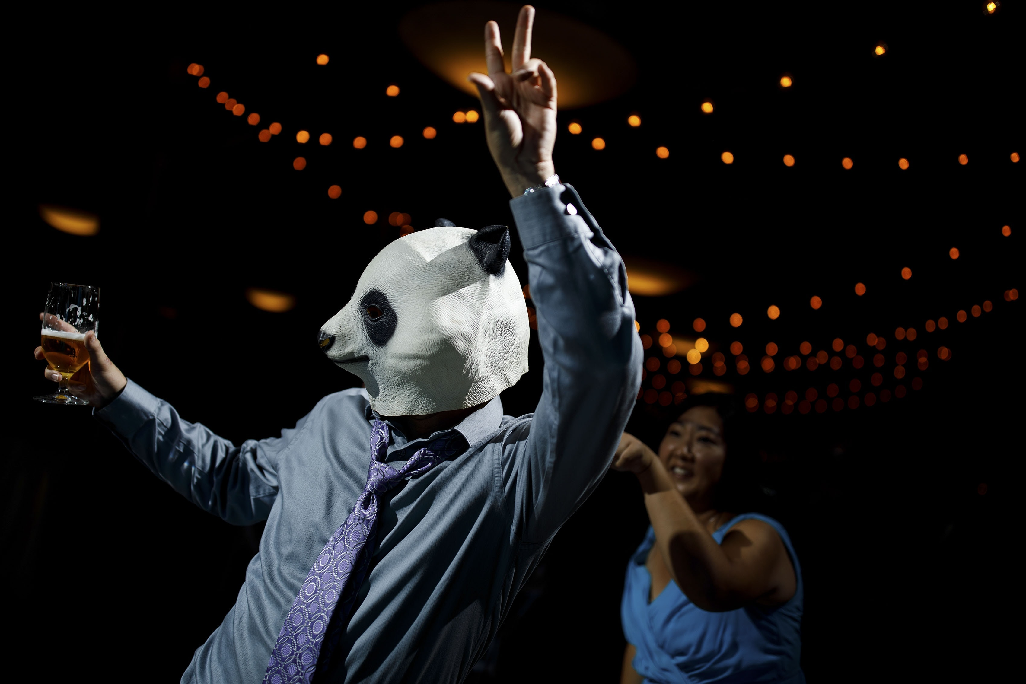 A wedding guest wears a panda mask while dancing at A Basin