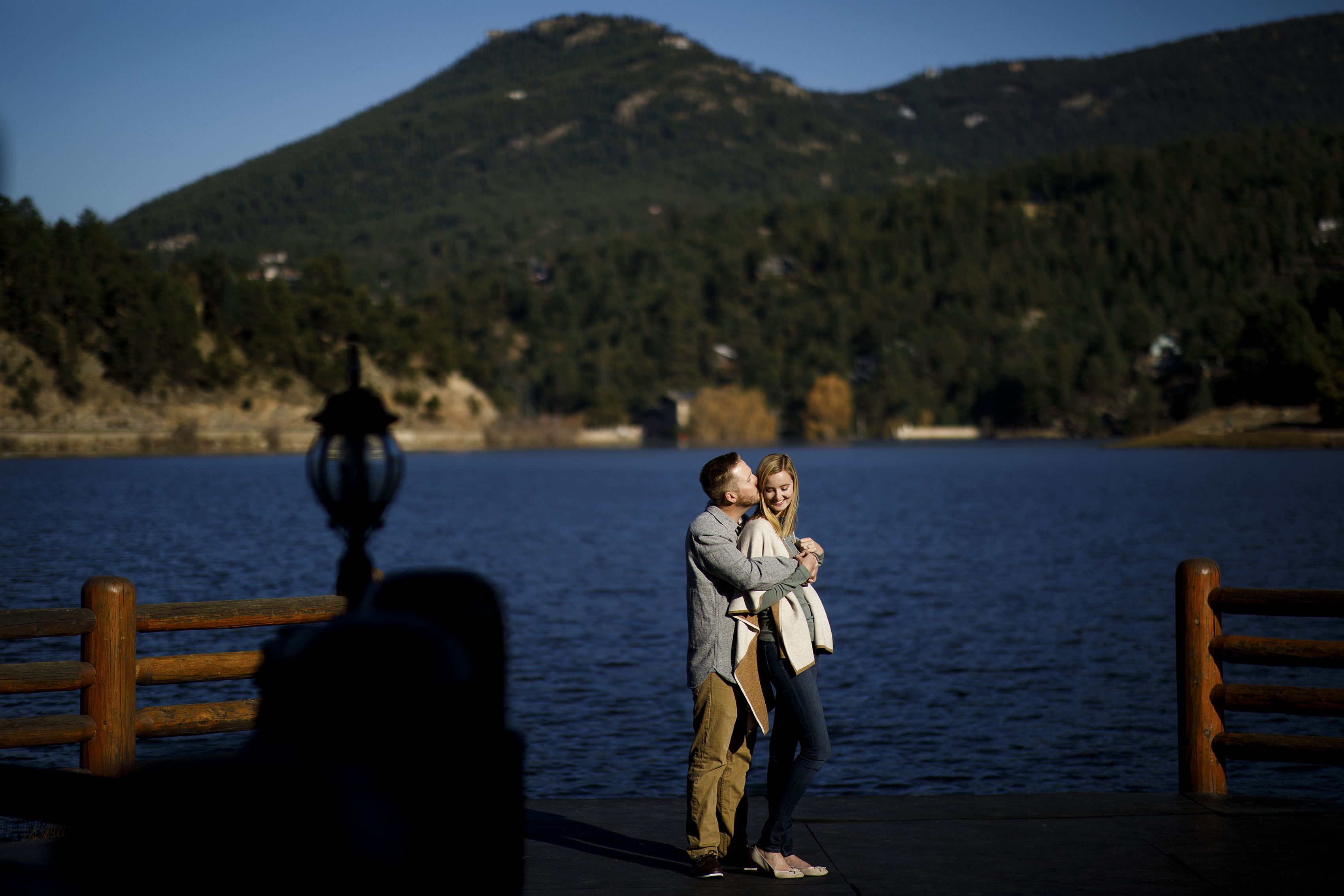 Stefan kisses Jennifer on the deck at the Evergreen Lake House during their fall engagement session
