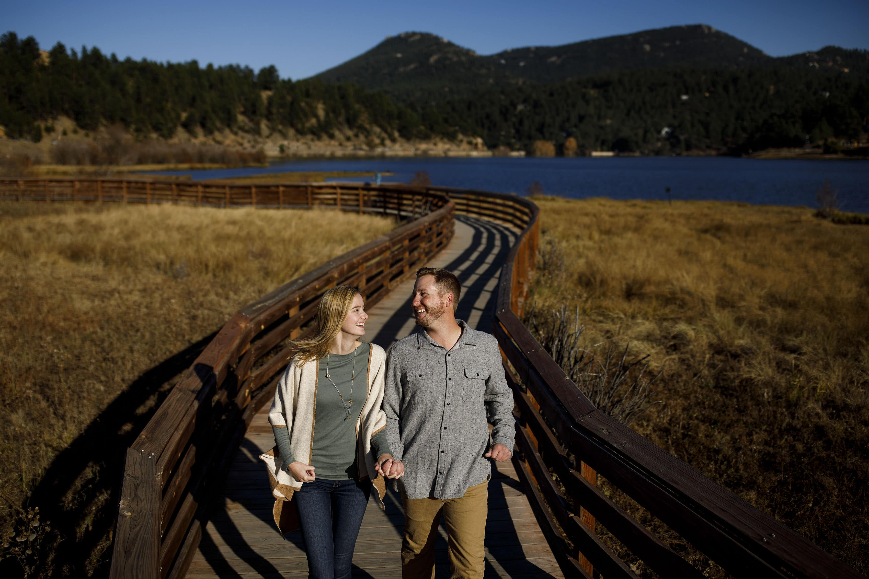 Jennifer and Stefan laugh together on the wooden path at Evergreen Lake during a fall day