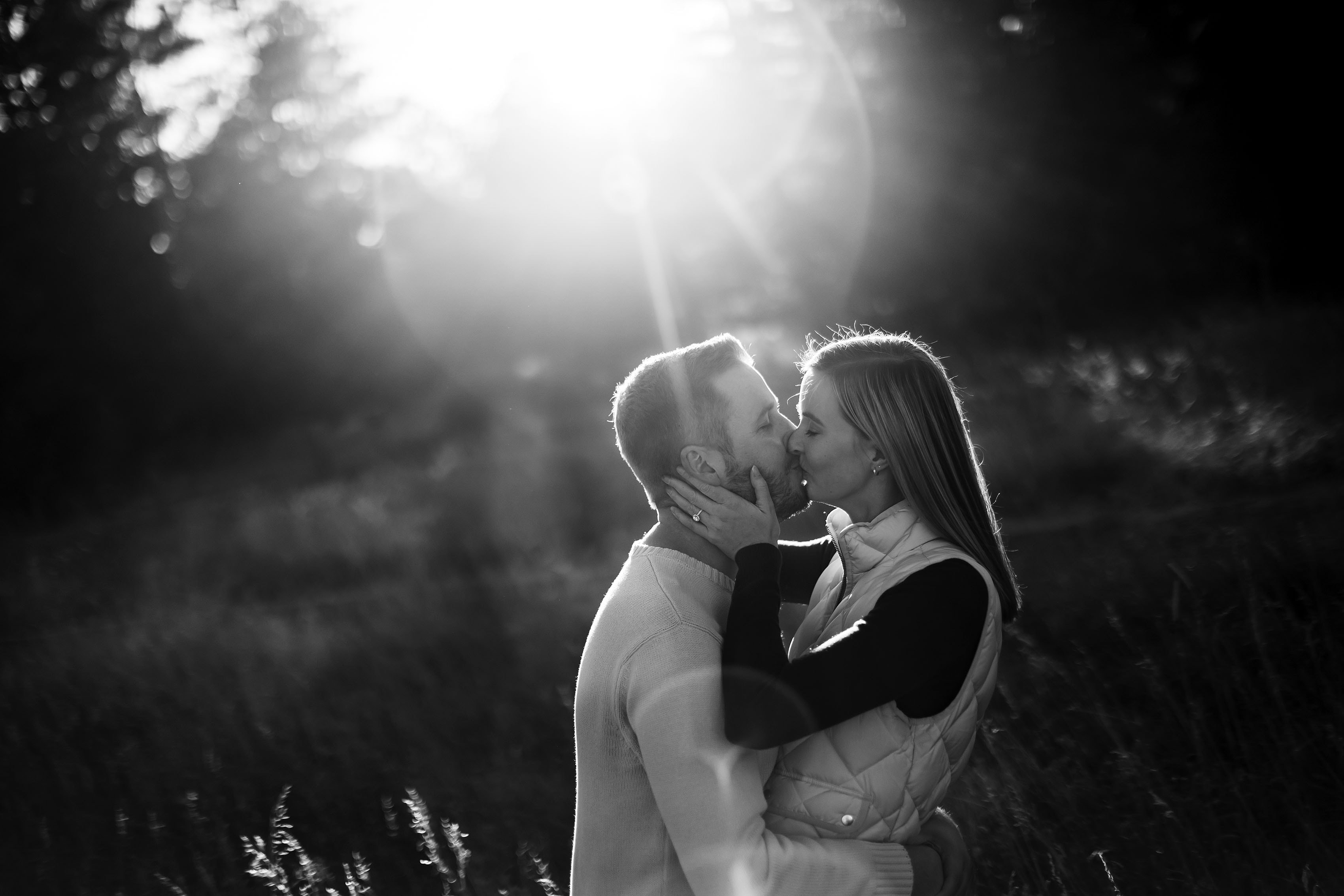 A couple kisses as the sun sets behind them in Evergreen, Colorado
