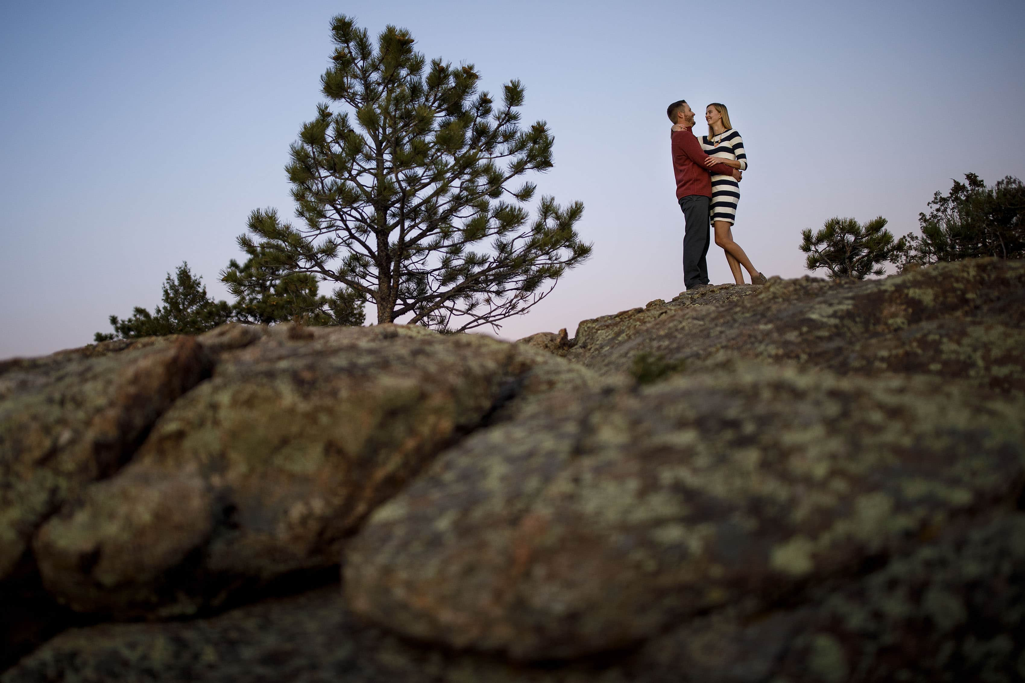 Jennifer and Stefan embrace on a rock during twilight at Alderfer Three Sisters Park