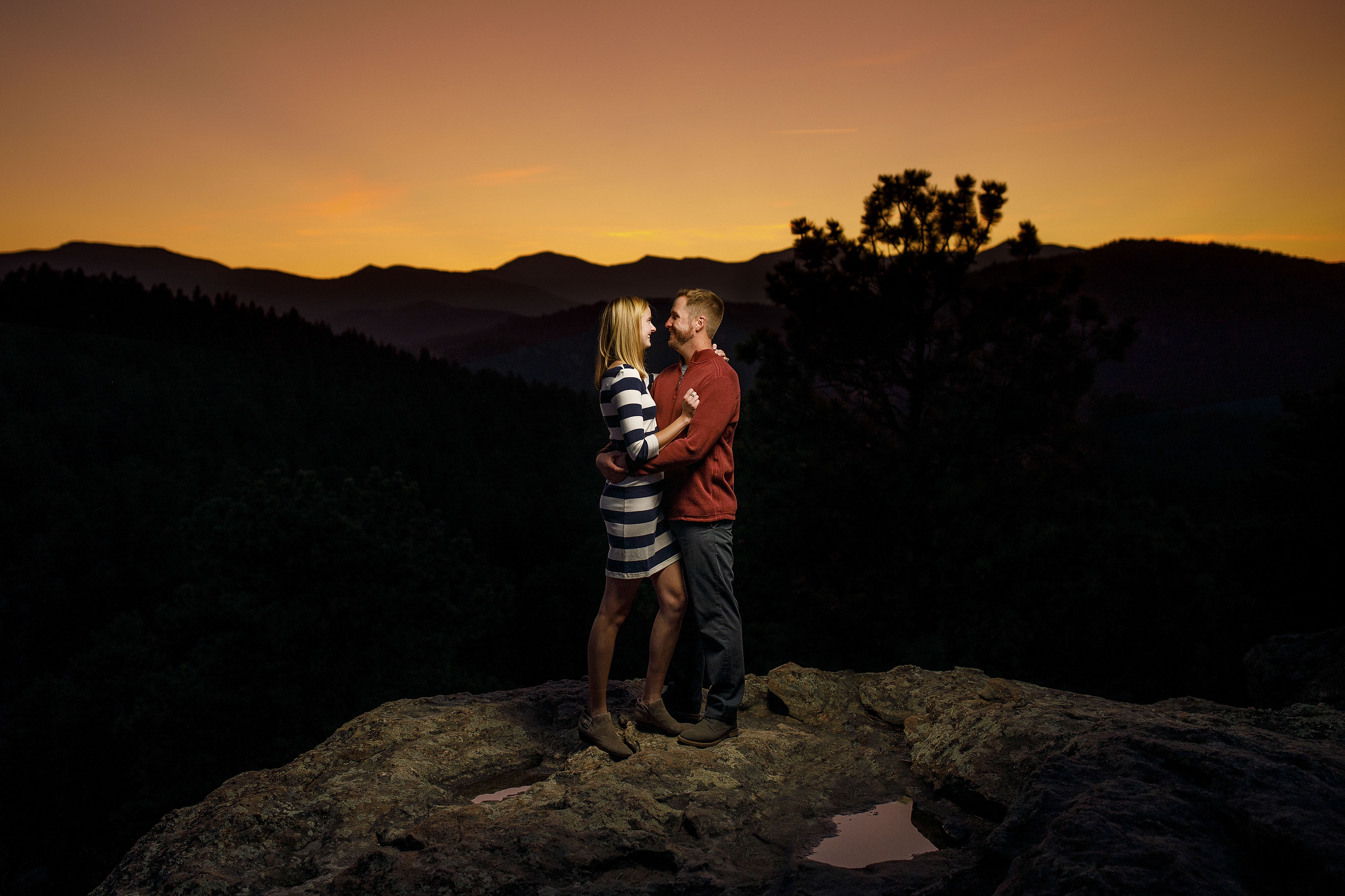 The sun sets behind a couple atop Brother's Lookout during their engagement photos at Alderfer Three Sister's Park in Evergreen, Colorado