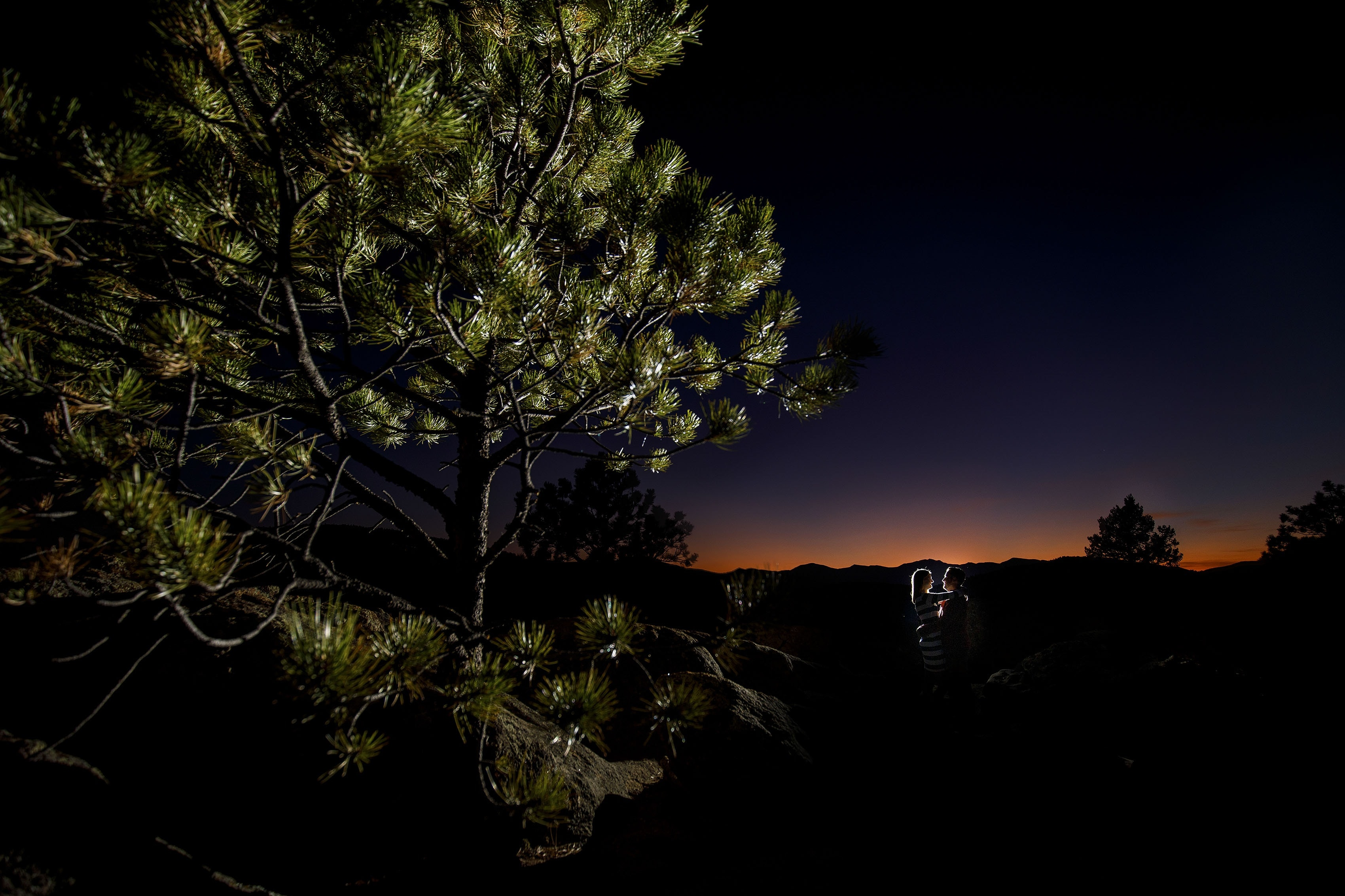 A couple is illuminated as the sun sets behind the mountains in Evergreen, Colorado