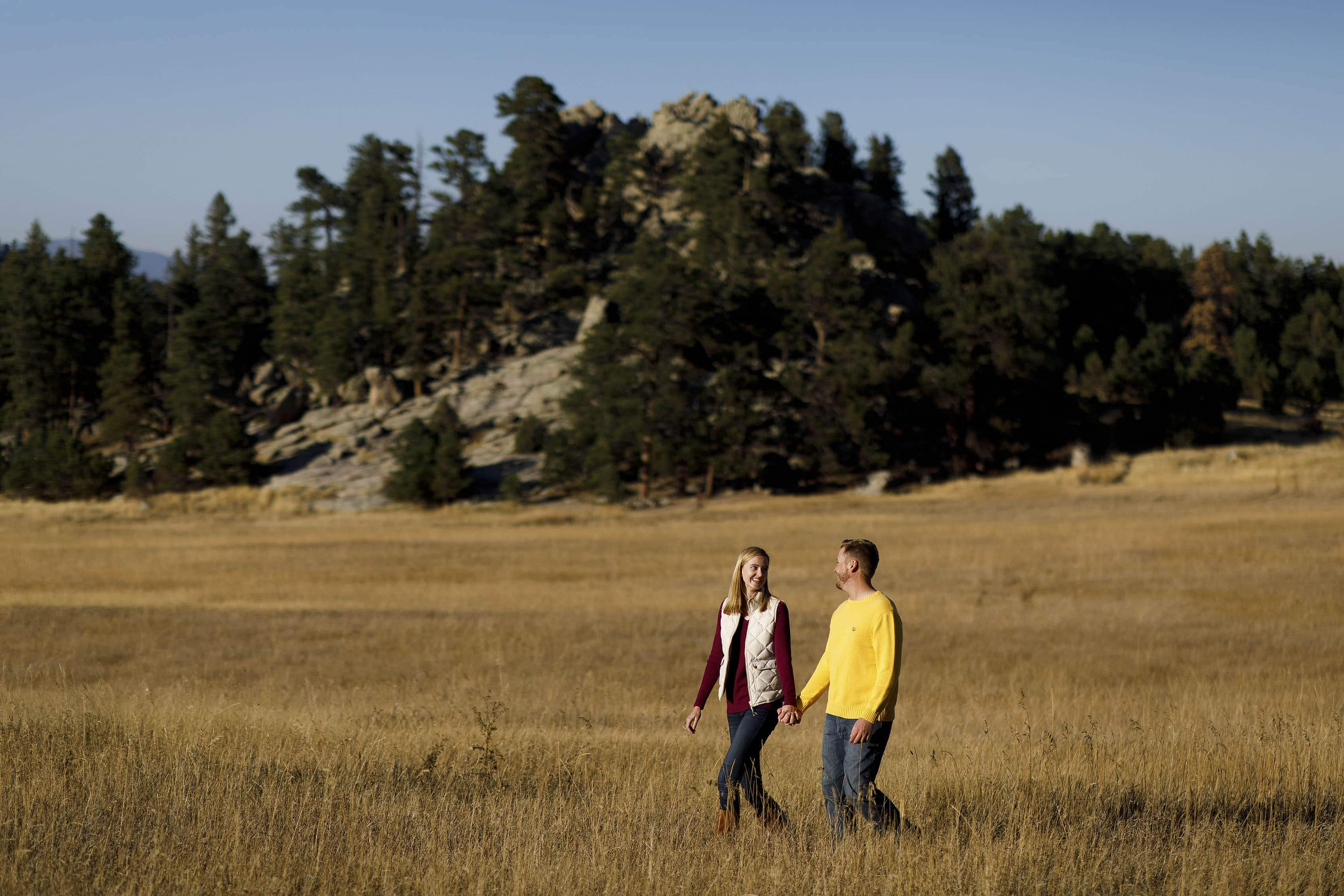 A couple walks together in the long grass at Alderfer Three Sister's Park in Evergreen, Colorado