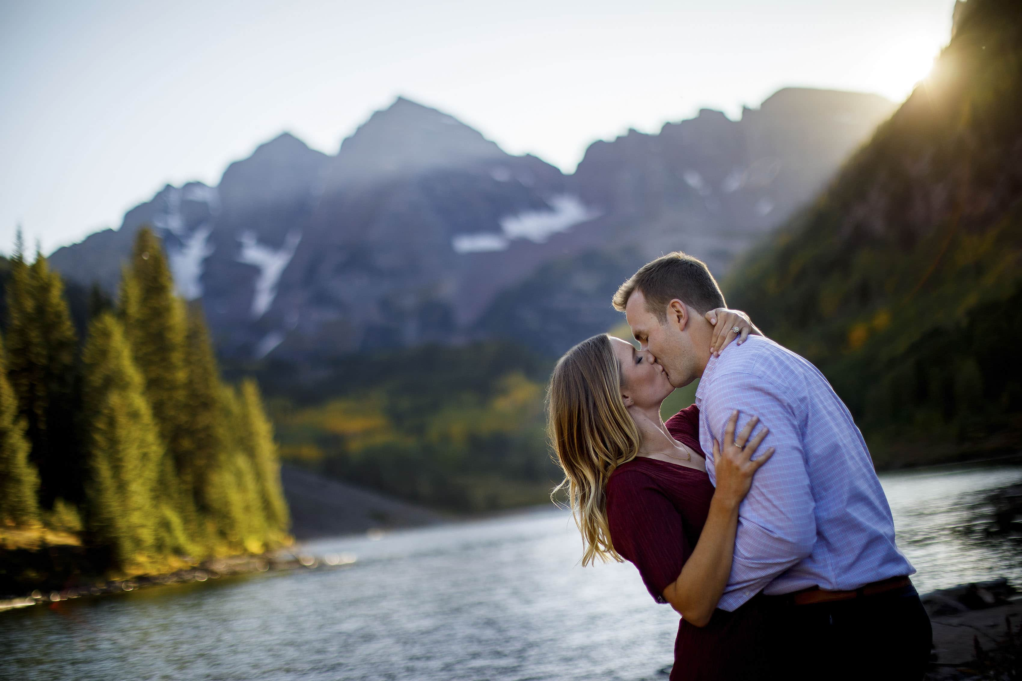 A couple share a kiss as the sun sets behind the Maroon Bells in Aspen in late September