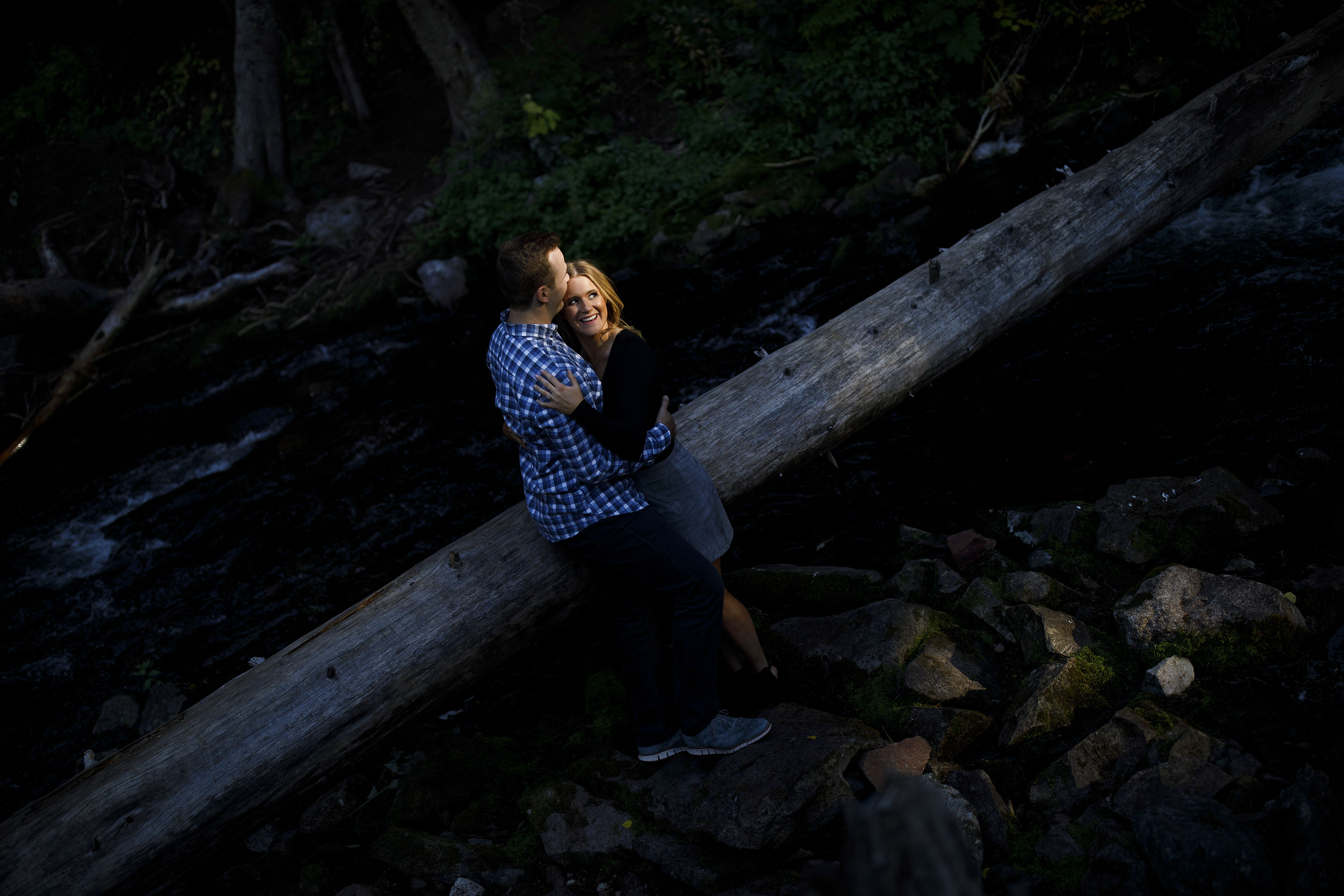 Drew kisses Mel in a pocket of light near West Maroon Creek in Aspen