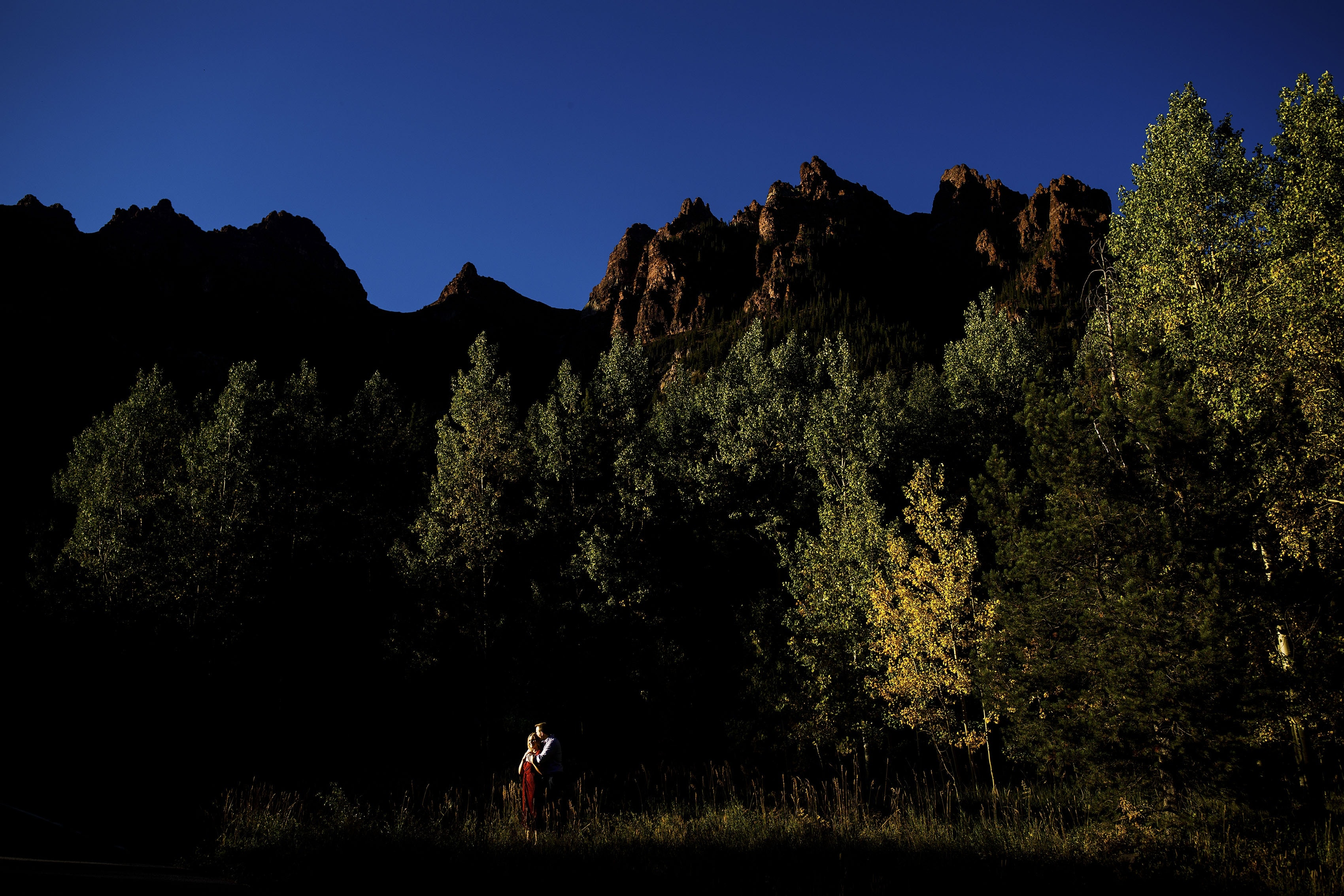 A couple pose together at the Maroon Bells during golden hour
