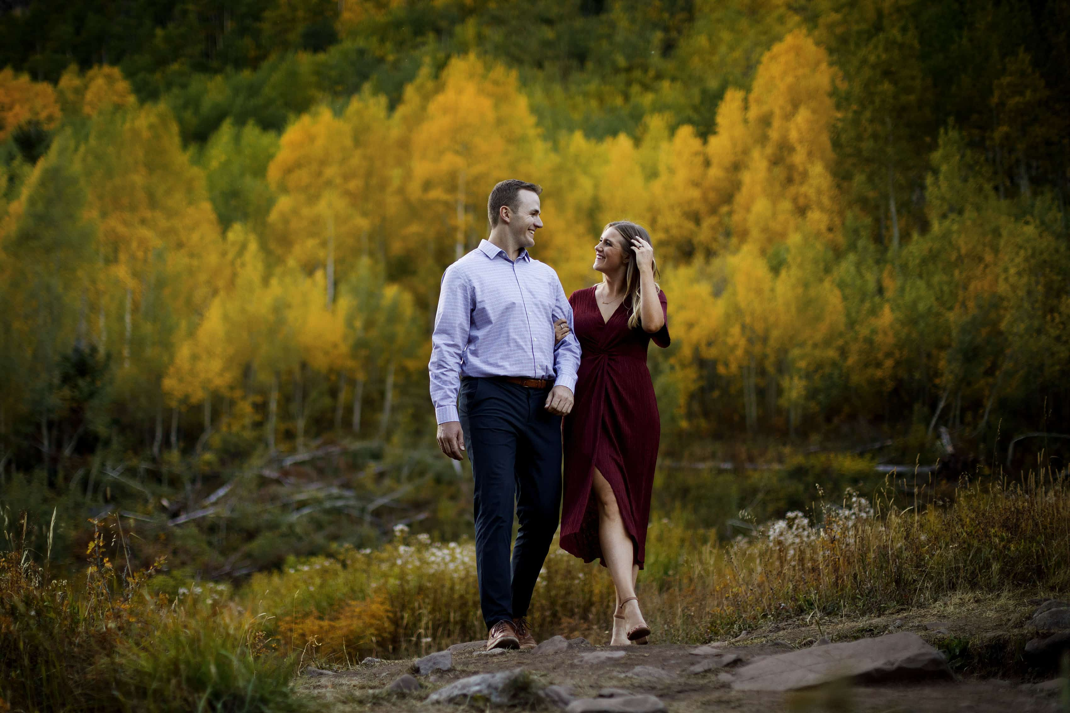 Drew and Mel walk together near a grove of colorful aspen trees during their fall engagement session in Aspen, Colorado.