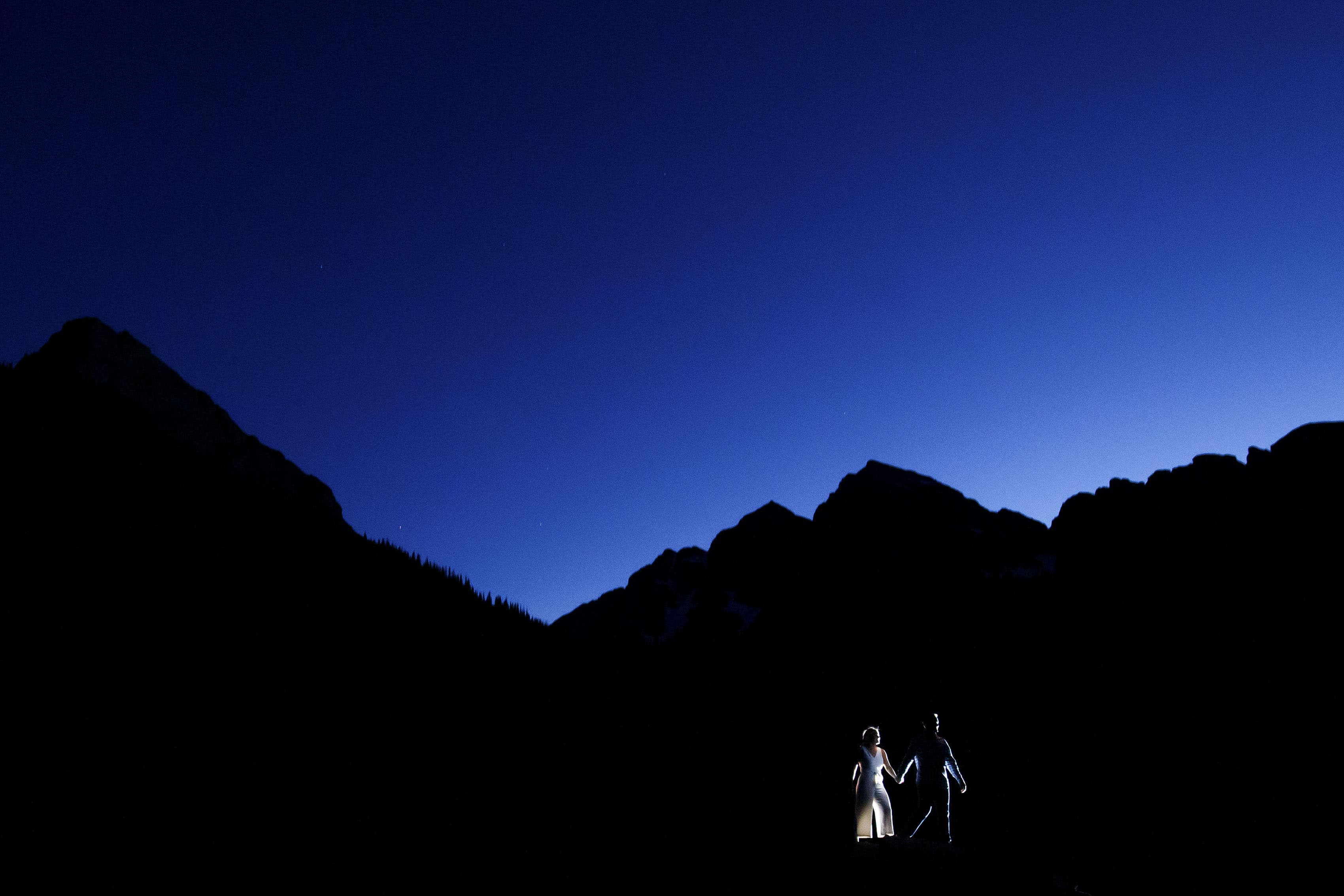Mel and Drew walk together at twilight at the Maroon Bells