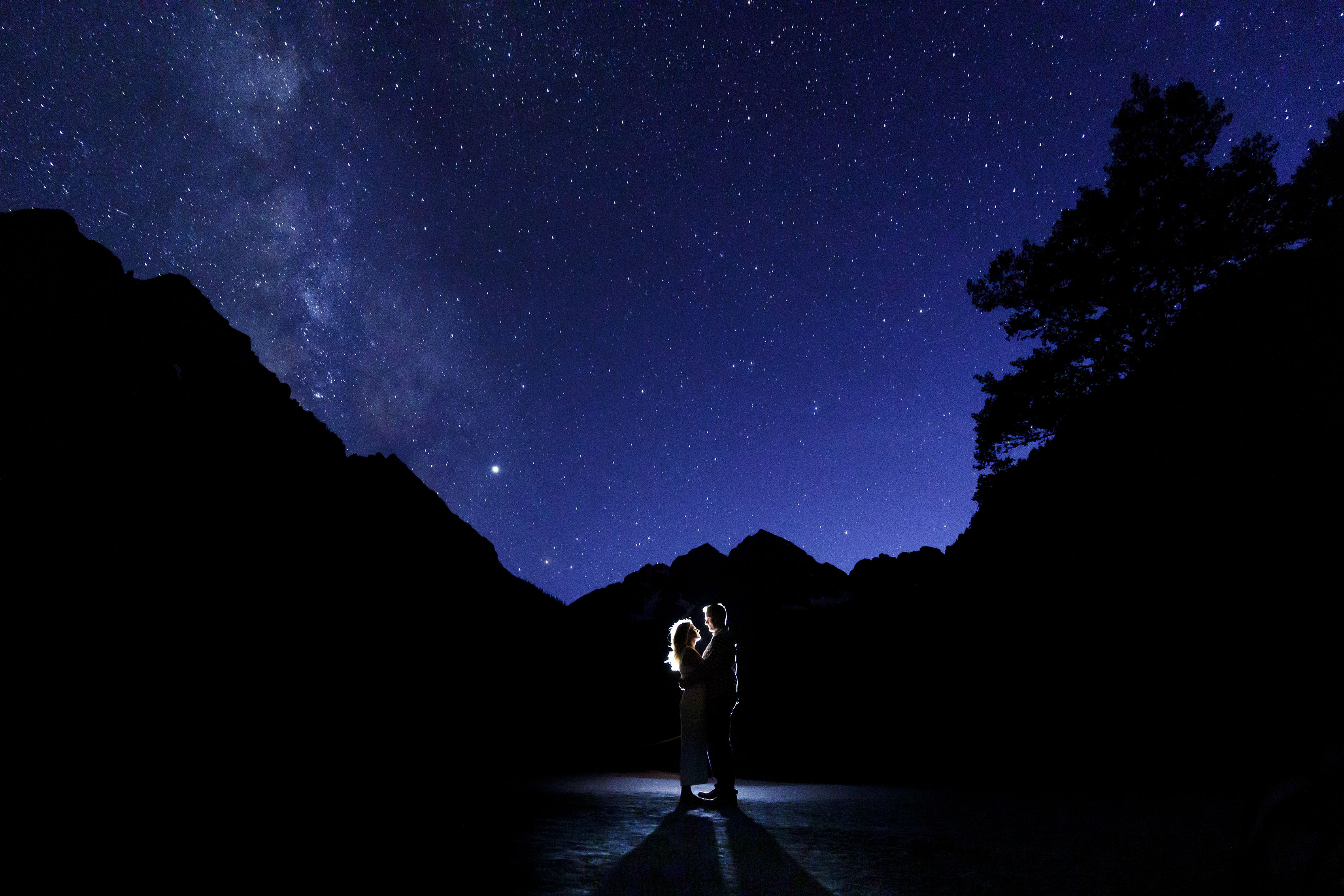 A couple poses under the stars at the Maroon Bells during their engagement photo session in Aspen, Colorado.