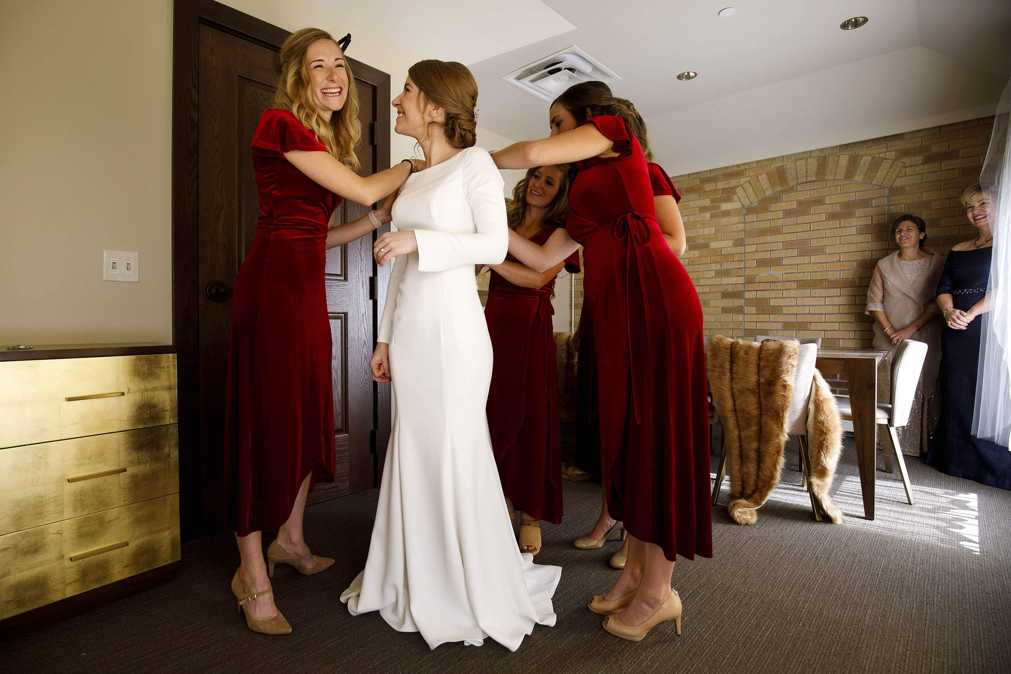The bride gets help putting on her dress in the bridal suite at Our Lady of Lourdes