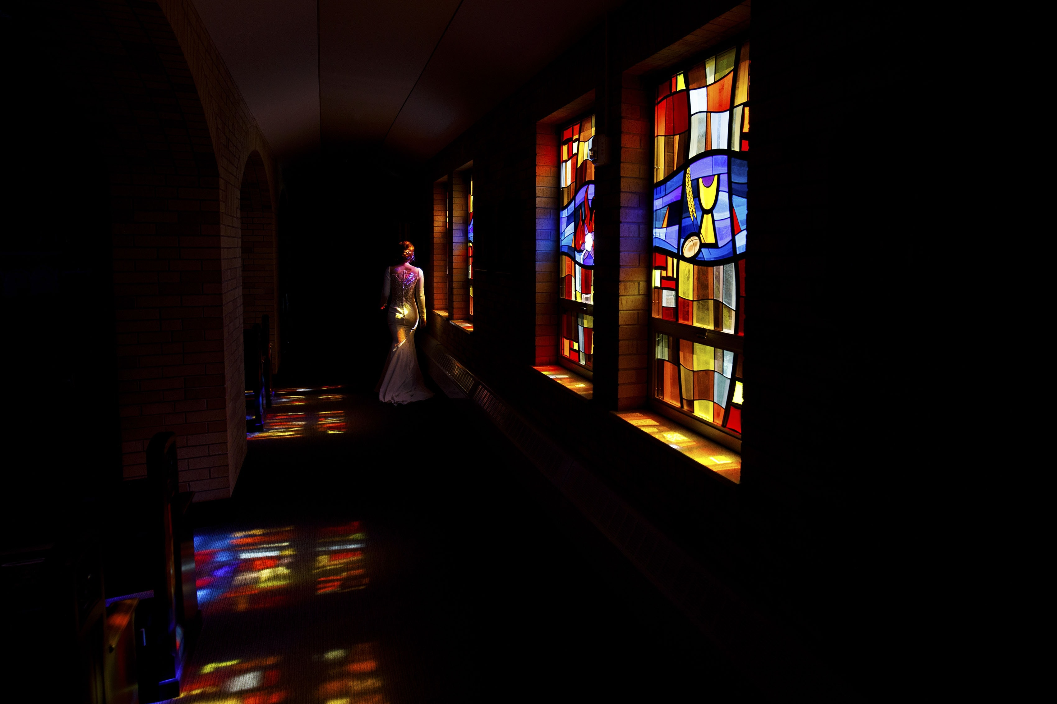 The bride walks down the stained glass hallway at Our Lady of Lourdes before her wedding