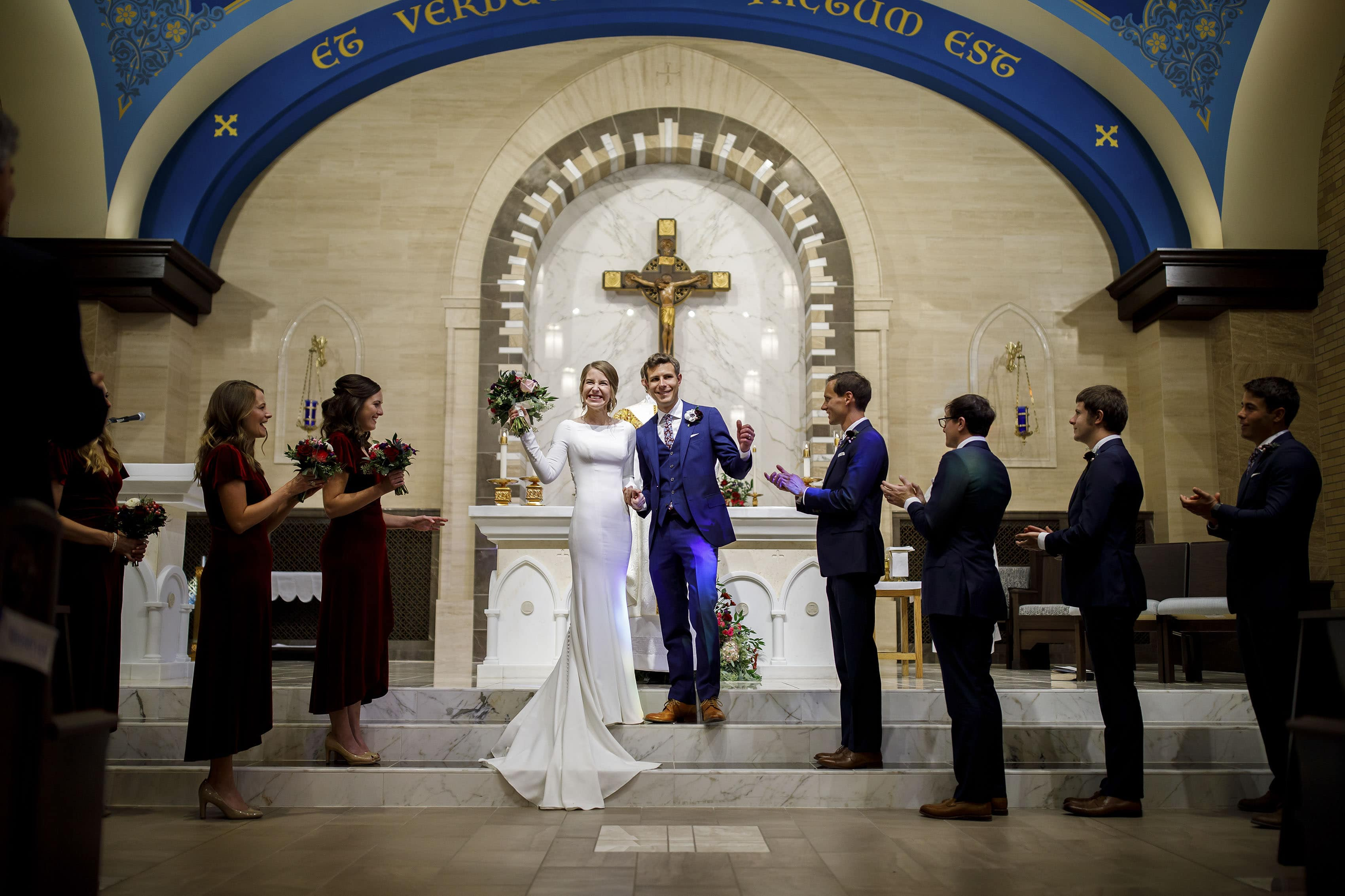 The couple celebrates during their wedding ceremony at Our Lady of Lourdes in Denver